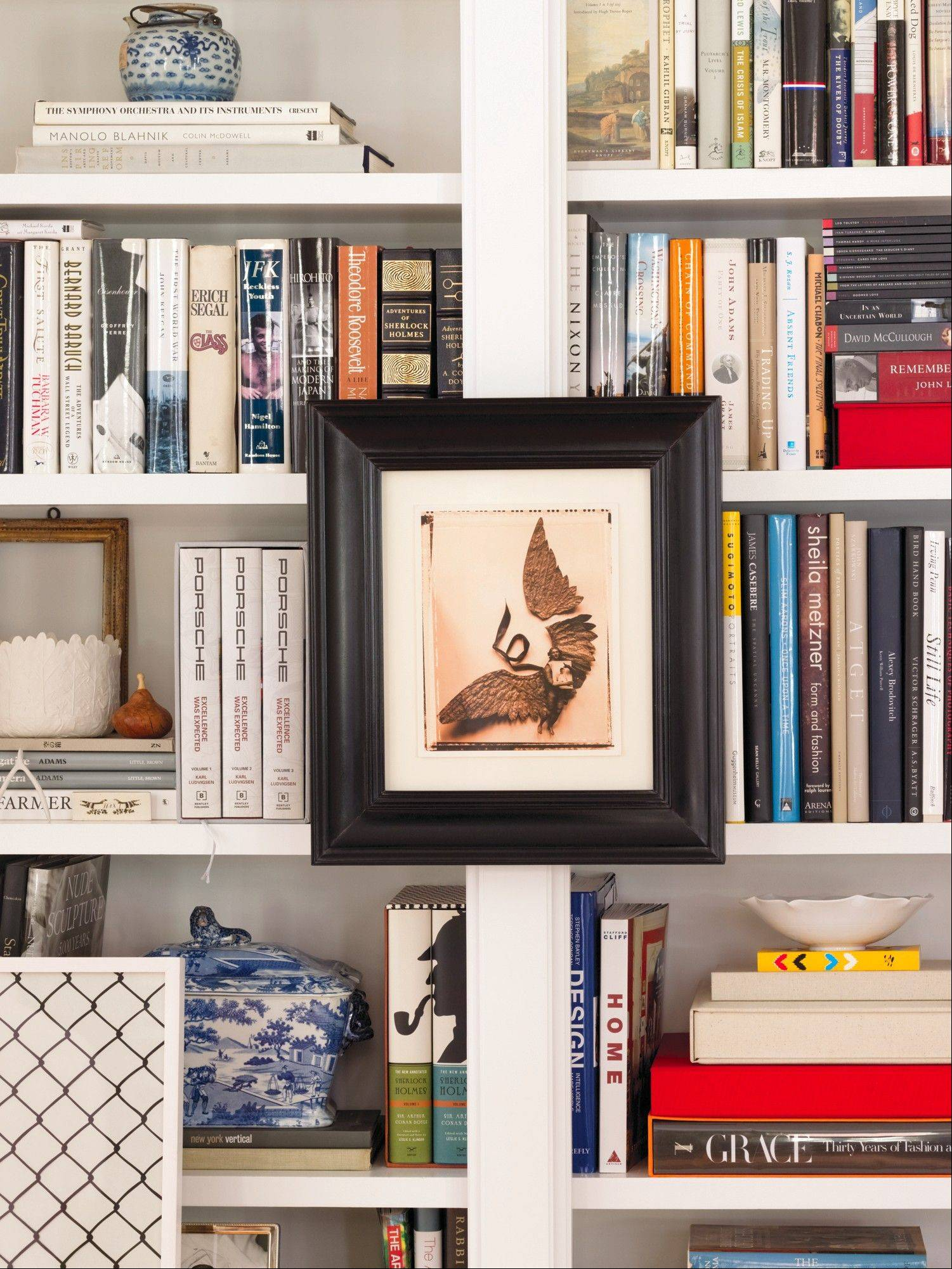 Artwork nicely complements the titles on Elizabeth Mayhew's bookshelves; photographs or ceramic objects can personalize a bookshelf.