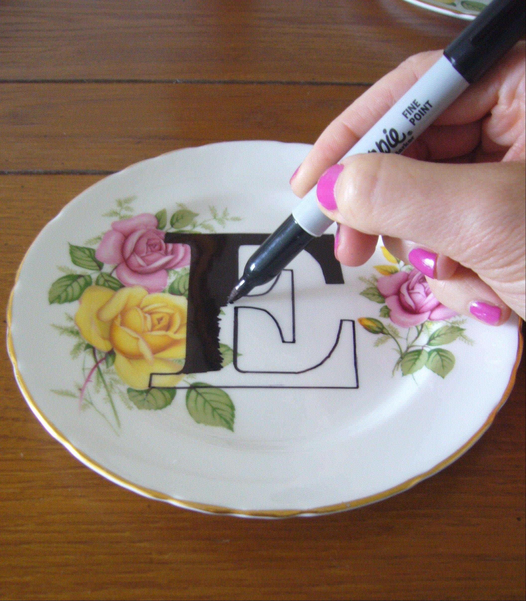"A vintage plate is upcycled with a modern letter ""E,"" filled in with a Sharpie, to complete a plate-decorating project."