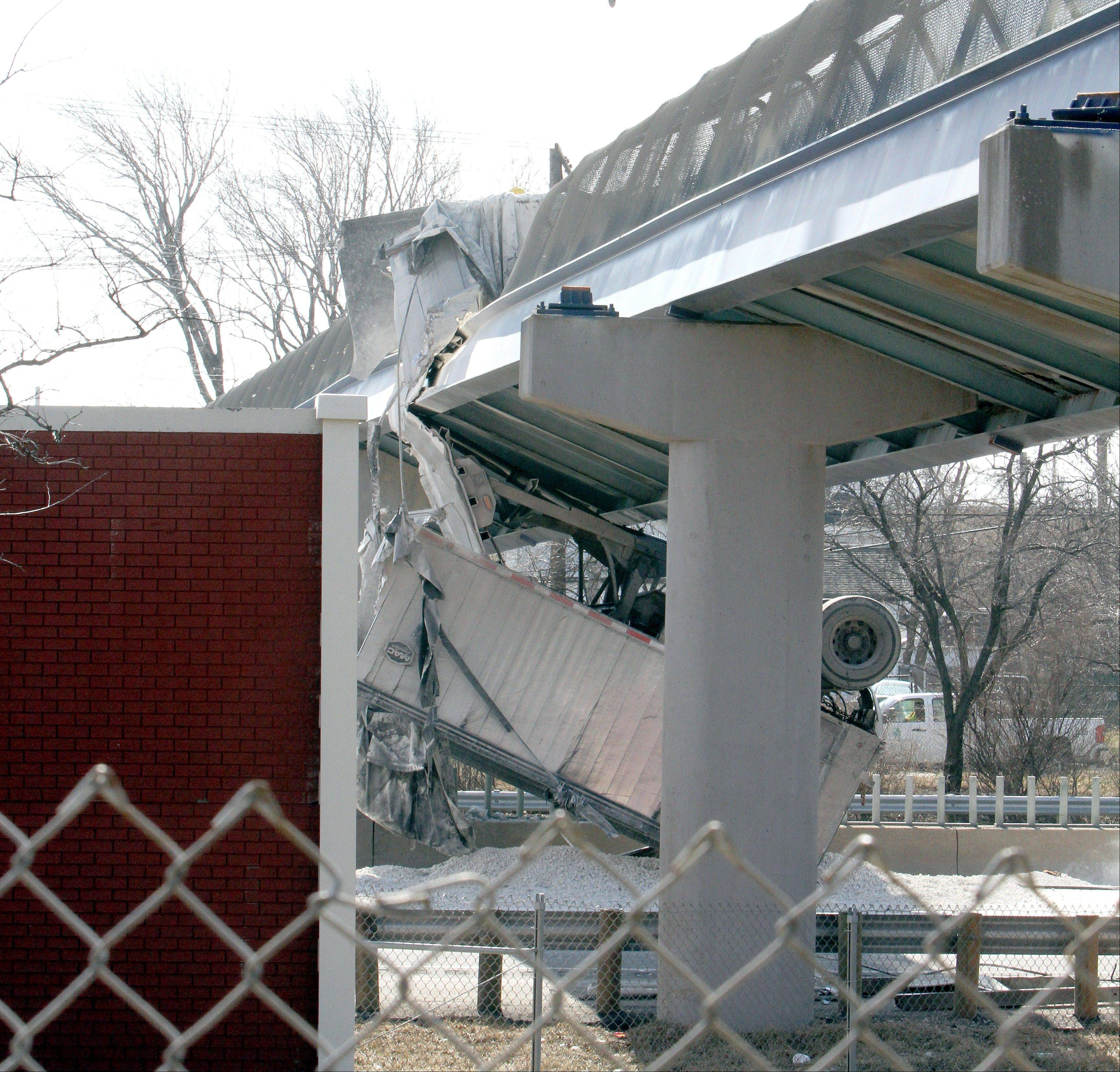 A dump truck is lodged underneath a pedestrian bridge Saturday over I-90 near E. 179 Street after its raised trailer struck the bridge, dumping its load and severely damaging the bridge.
