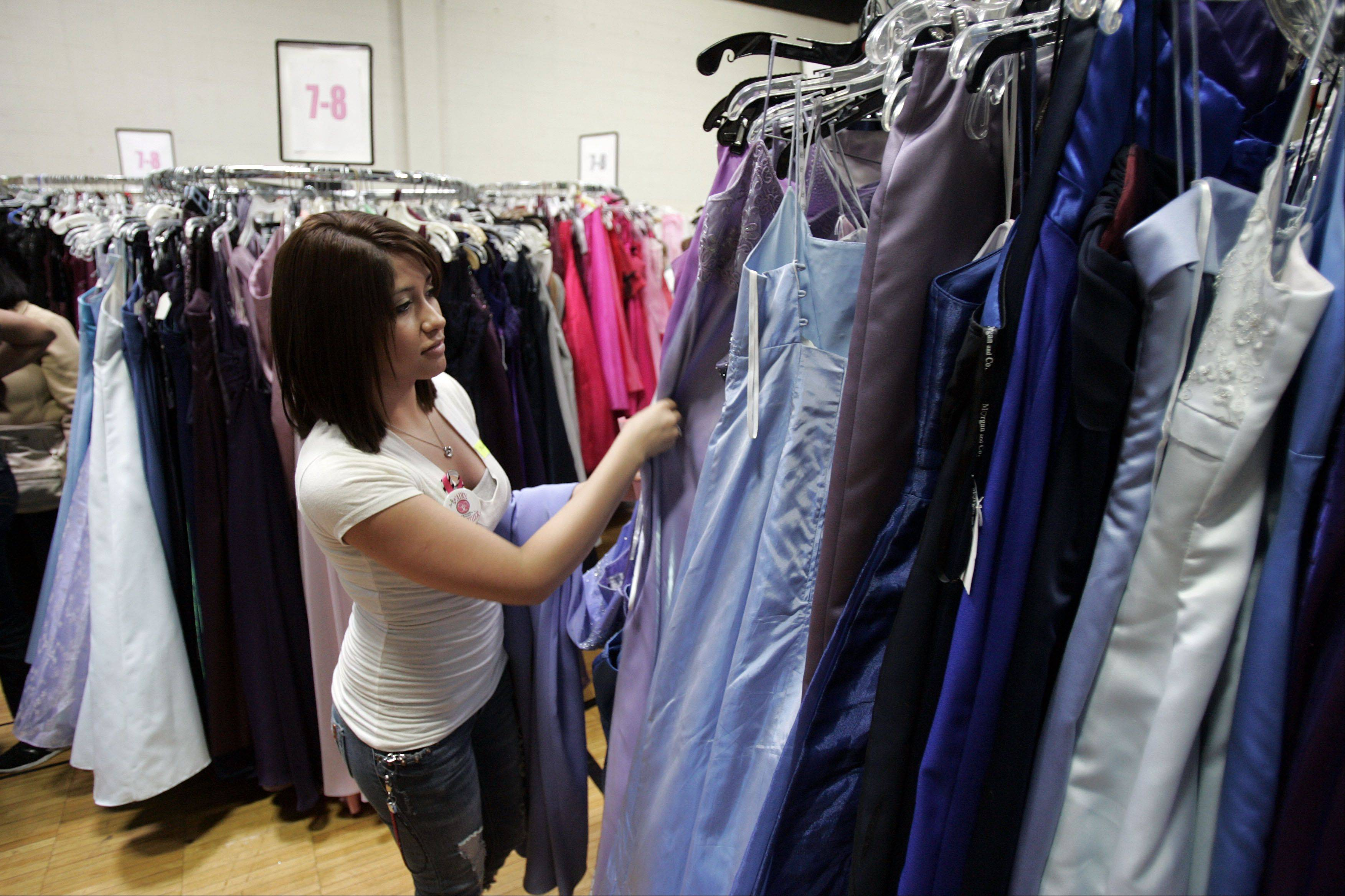 "Maria Pasillas, a first time ""Fairy Godmother"" volunteer, helps a high school student pick from more than 4,000 dresses during the annual Cinderella's Closet event Saturday at the YWCA in Elgin."