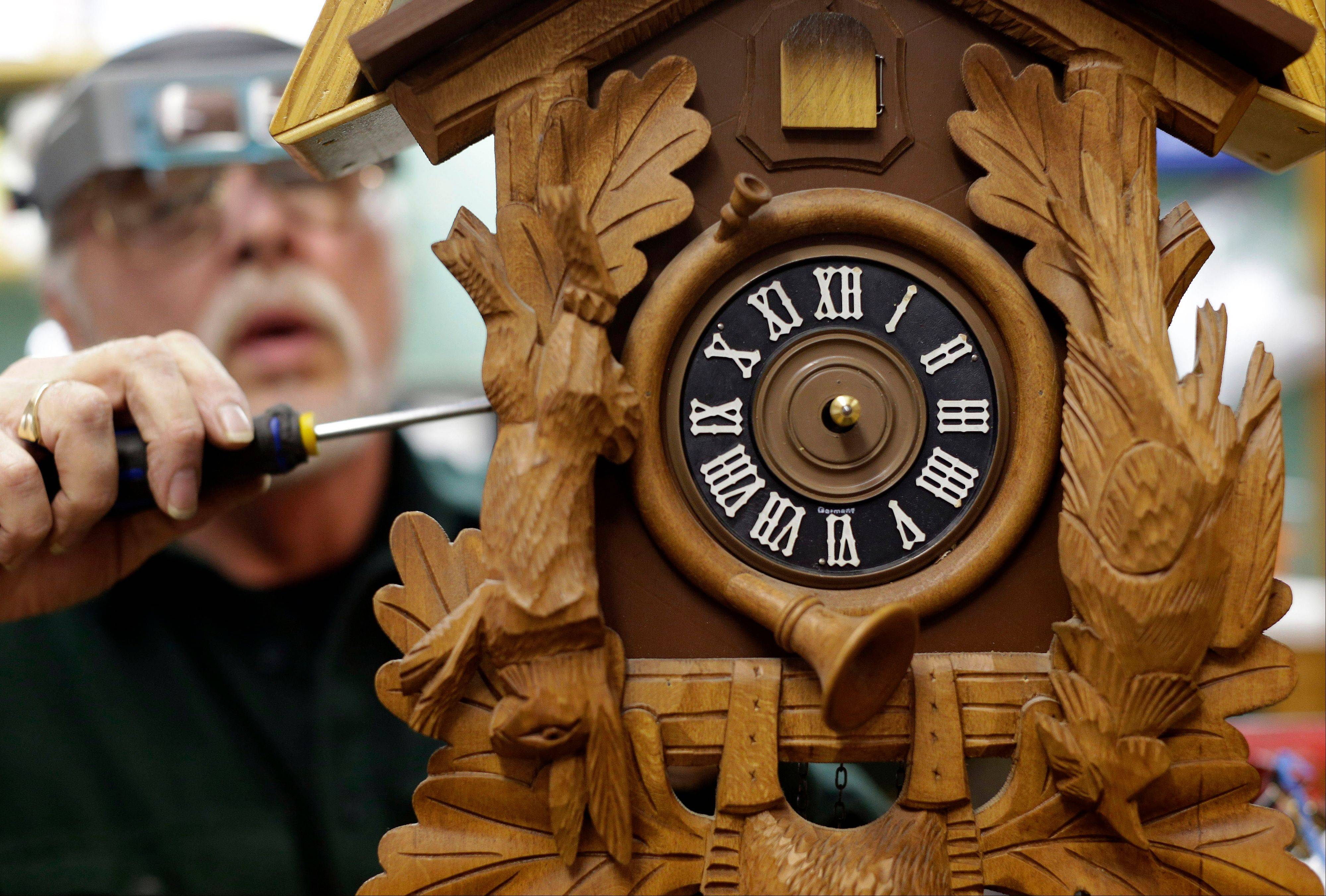 Ken Peters repairs a cuckoo clock Friday in Hands of Time, a clock store and repair shop in Savage, Md.
