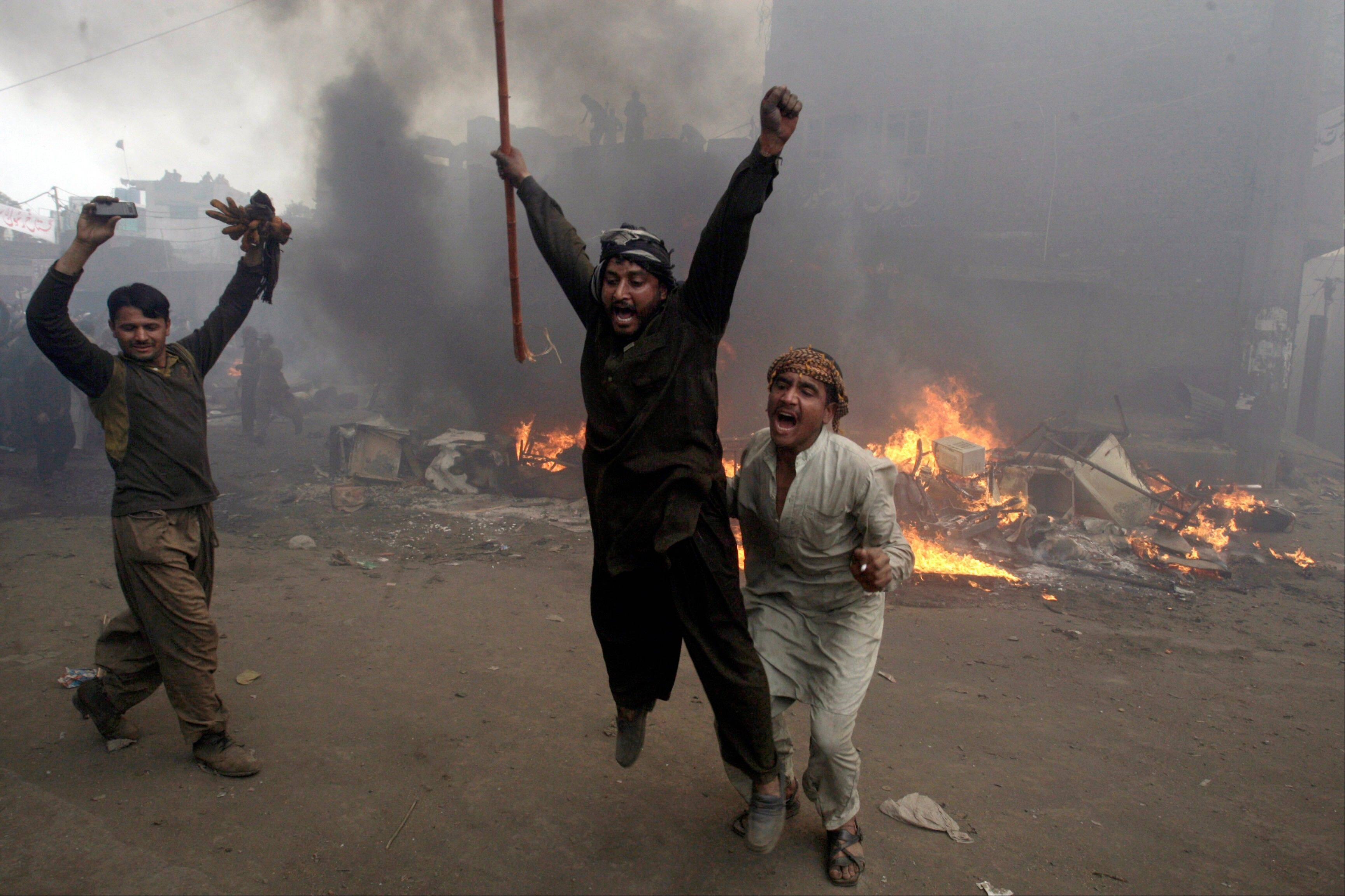 Pakistani men, part of an angry mob, run Saturday after burning belongings of Christian families, in Lahore, Pakistan.