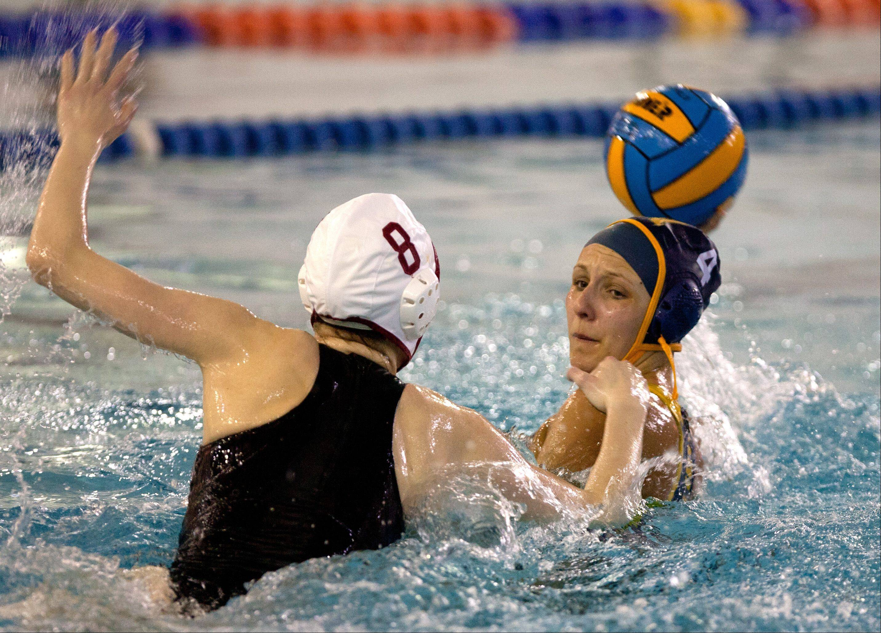 Naperville Central's Erin Reagan, left, defends Neuqua Valley's Morgan Miller, right, during the Naperville Quint girls varsity water polo tournament.