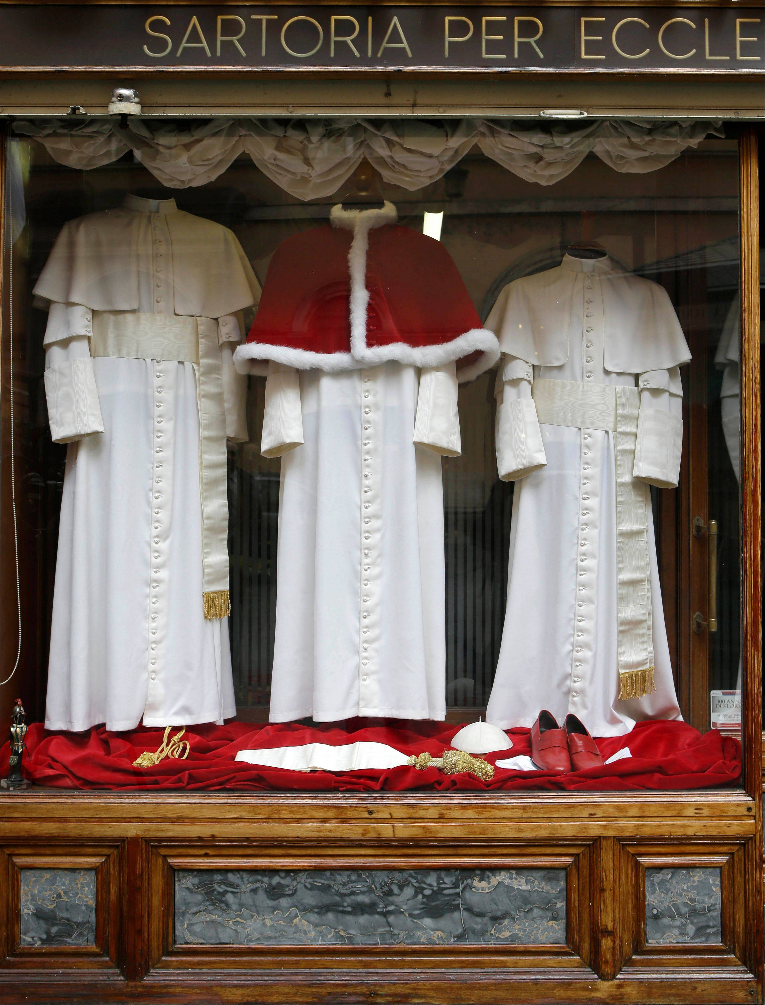 Three sets of papal outfits — small, medium and large sizes — are displayed in the window of the tailoring shop Gammarelli in Rome.