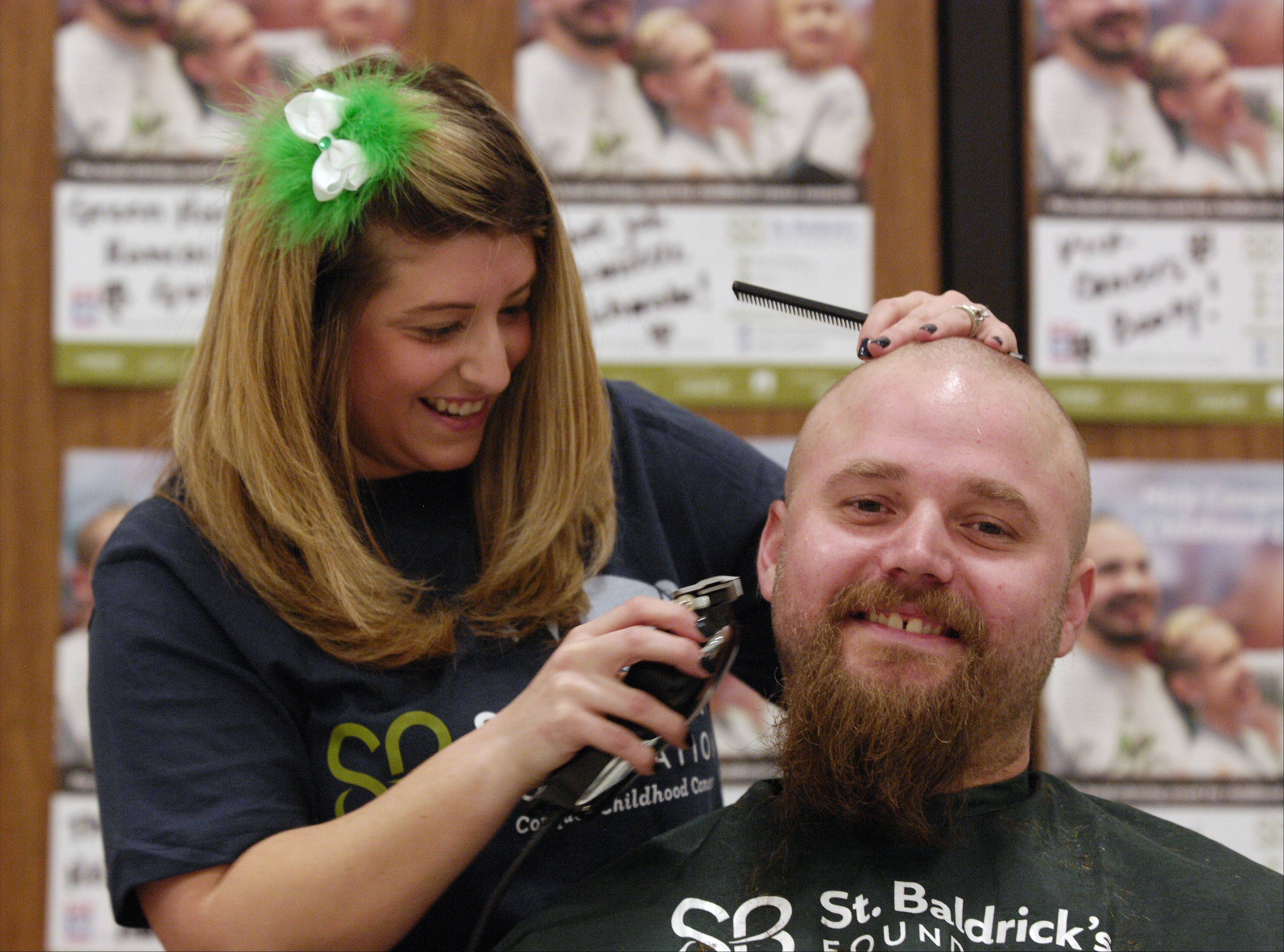 Gina Barzso of Bartlett shaves the head and bread of her husband Dan Barzso during the St. Baldrick�s Day shaving event at Evergreen Elementary School in honor of third grader Jack O�Donoghue, who�s cancer is now in remission. This is Barzso�s first time volunteering to shave heads for a St. Baldrick�s Day event.