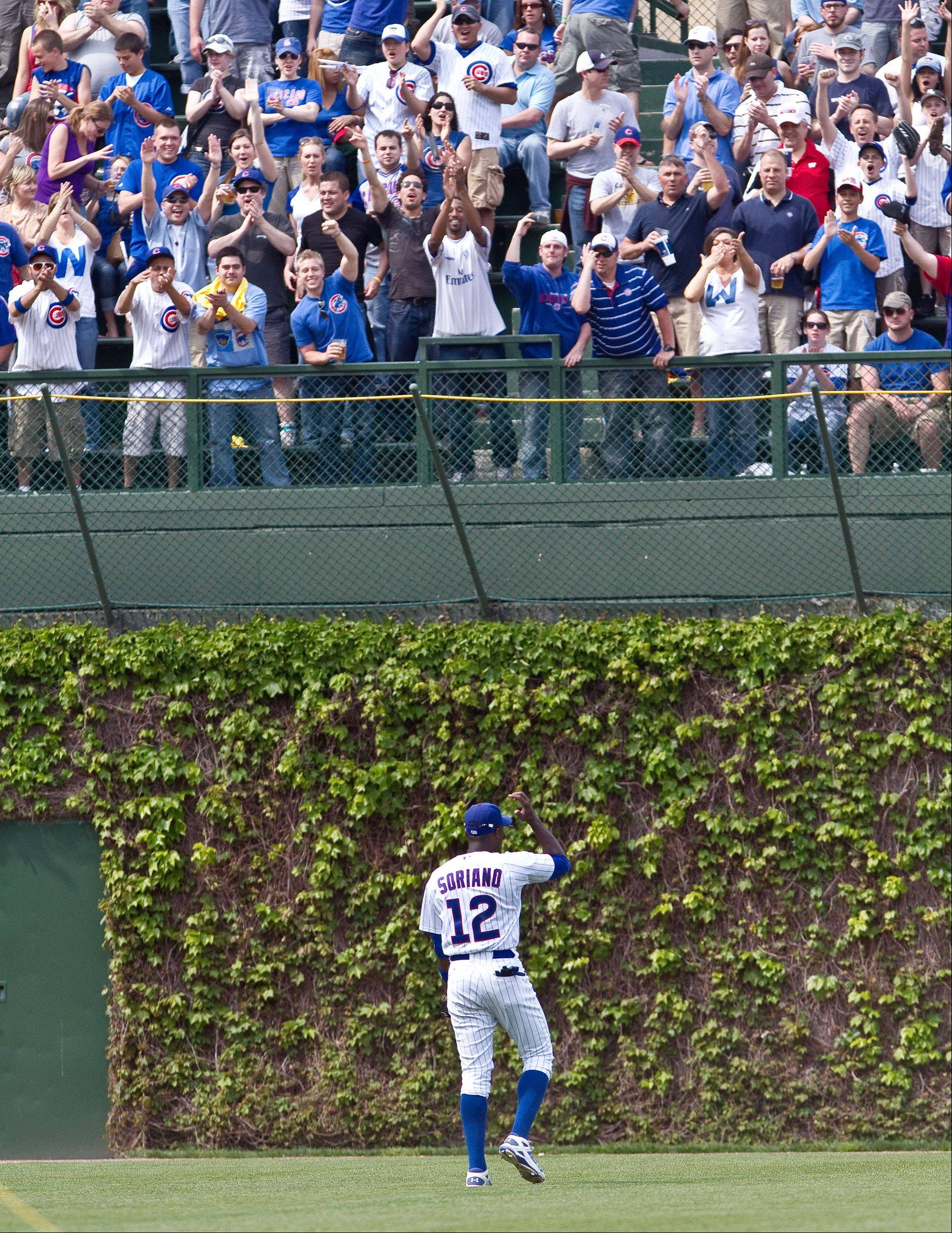 Alfonso Soriano acknowledges the cheering crowd in the left field bleachers as he takes his position during a game against Arizona in 2010. Soriano�s outfield play improved greatly in 2012 once he began to respect the Cubs� new coaching staff.