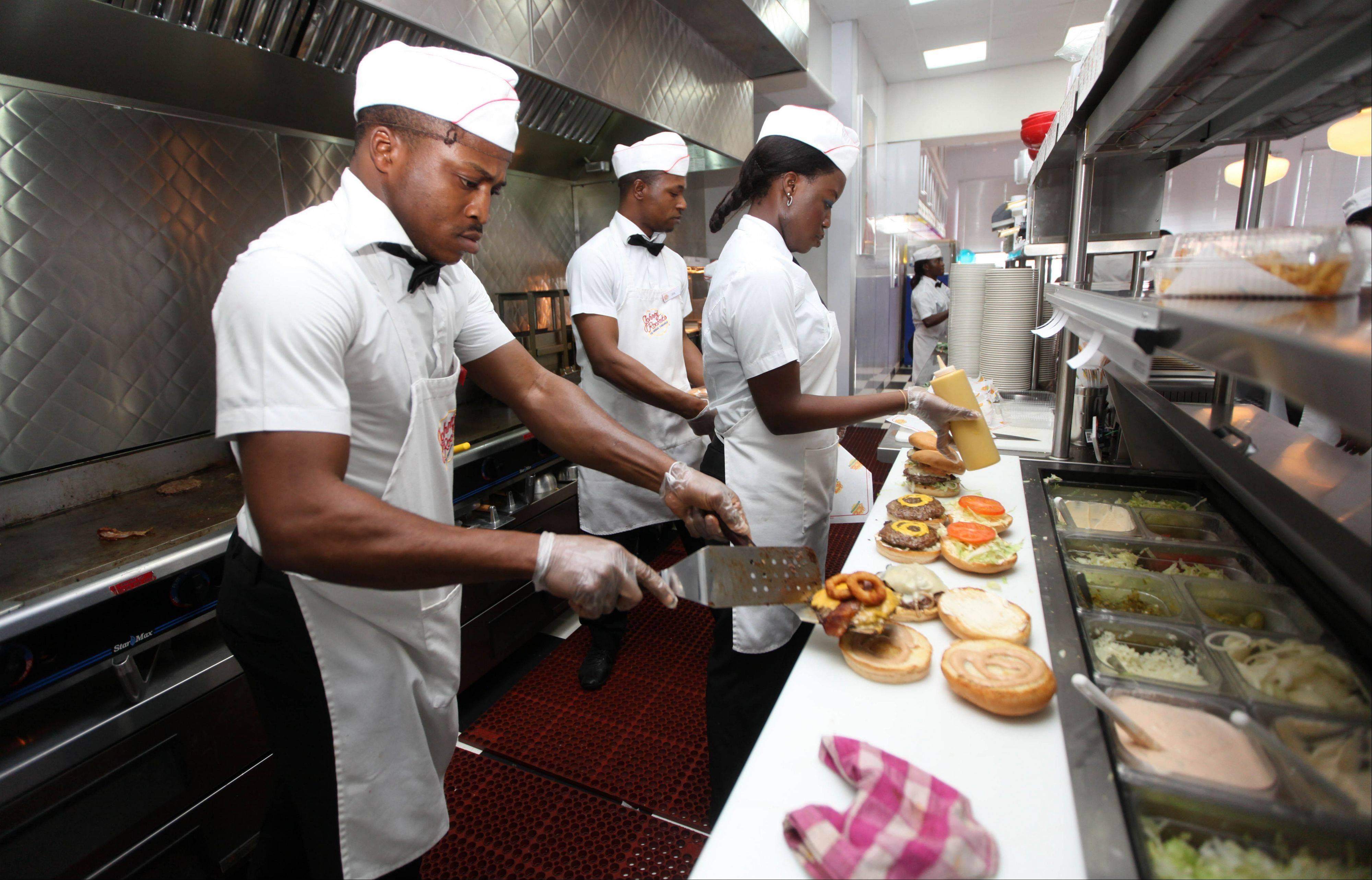 Workers prepare hamburgers at Johnny Rockets restaurant in Lagos, Nigeria.