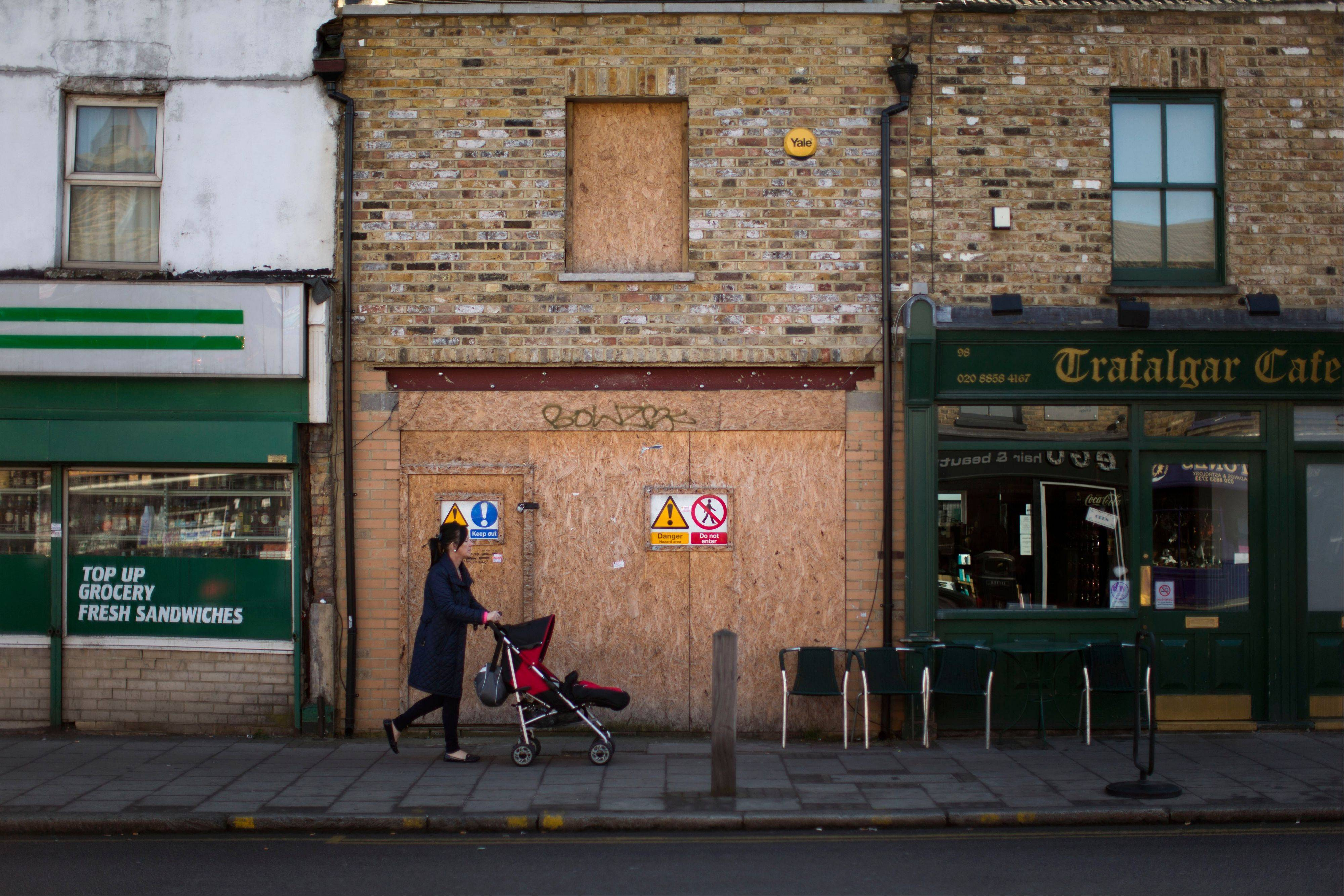 A woman pushes a child's buggy past a boarded up shop front on Trafalgar Road in Greenwich, London.