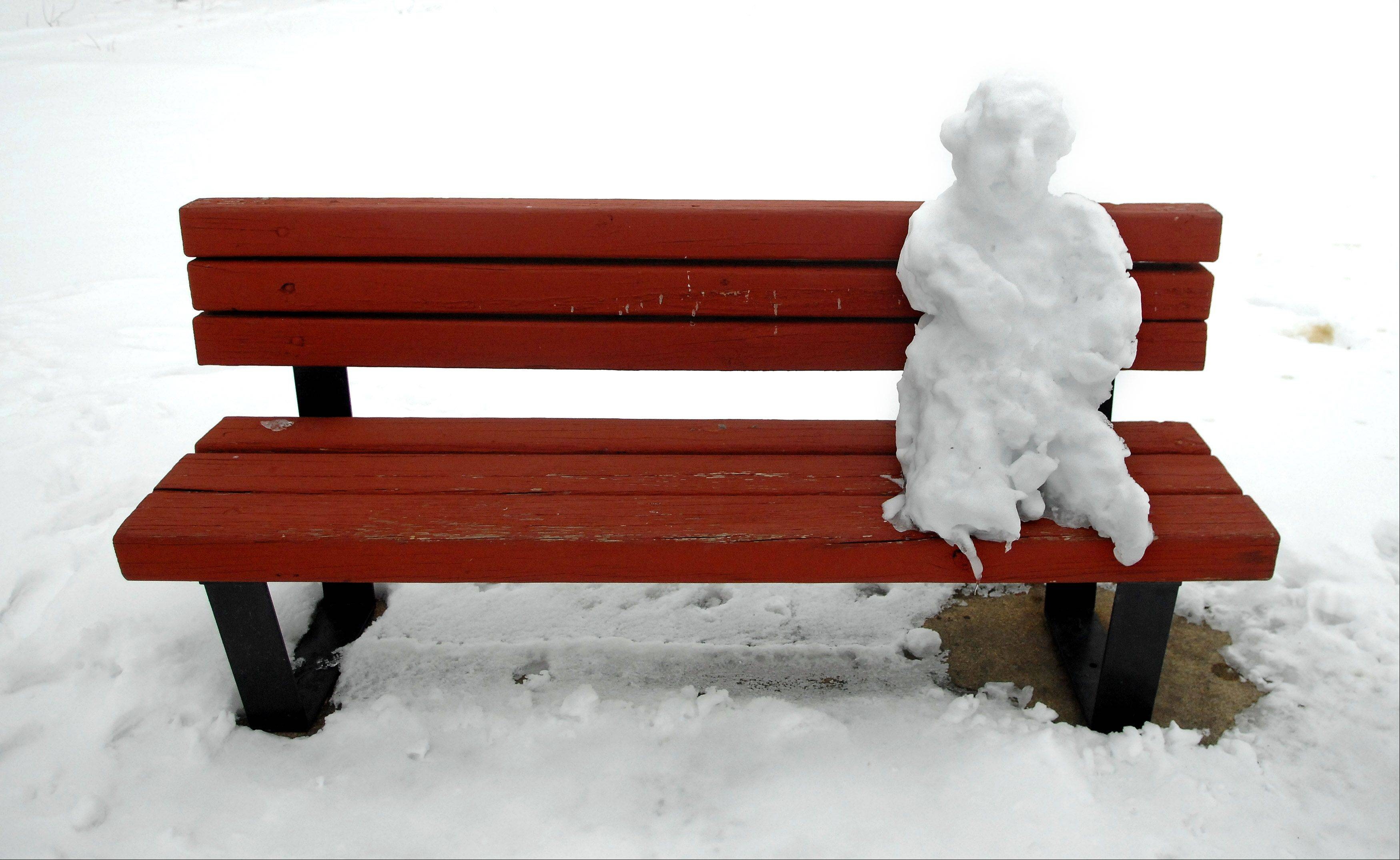 A snowman perched on a bench is the only sign of life at Ferson Creek Park in St. Charles Monday morni