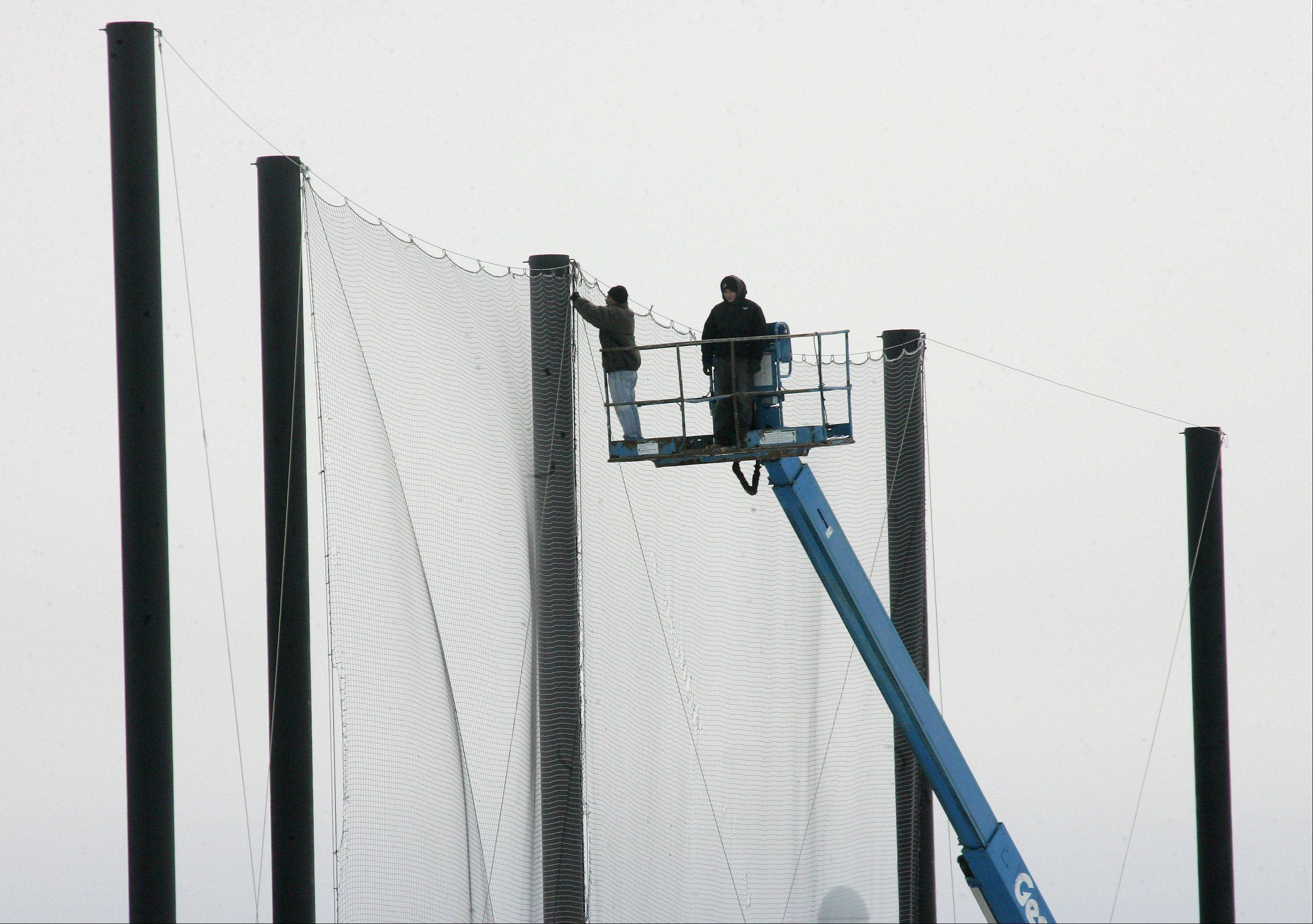 Sergio Pagan, left, and Jose Rivera, of PSE Netting, repair the baseball back stop at Vernon Hills High School Monday in preparation for the upcoming season.