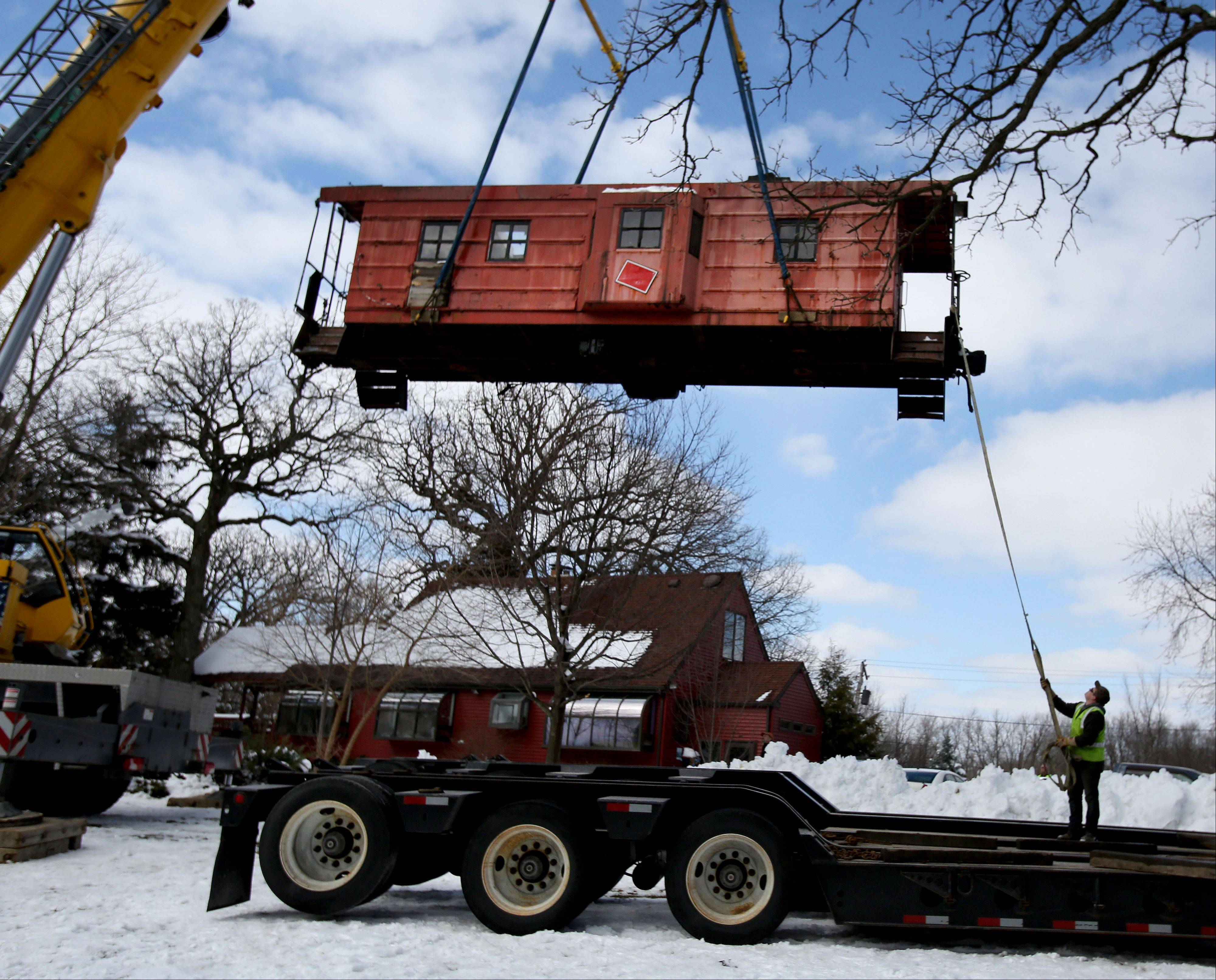 A caboose is lifted onto a flatbed truck on Thursday in Itasca. It was moved from its home on Bloomingdale Road for its new home at the Itasca Depot Museum.