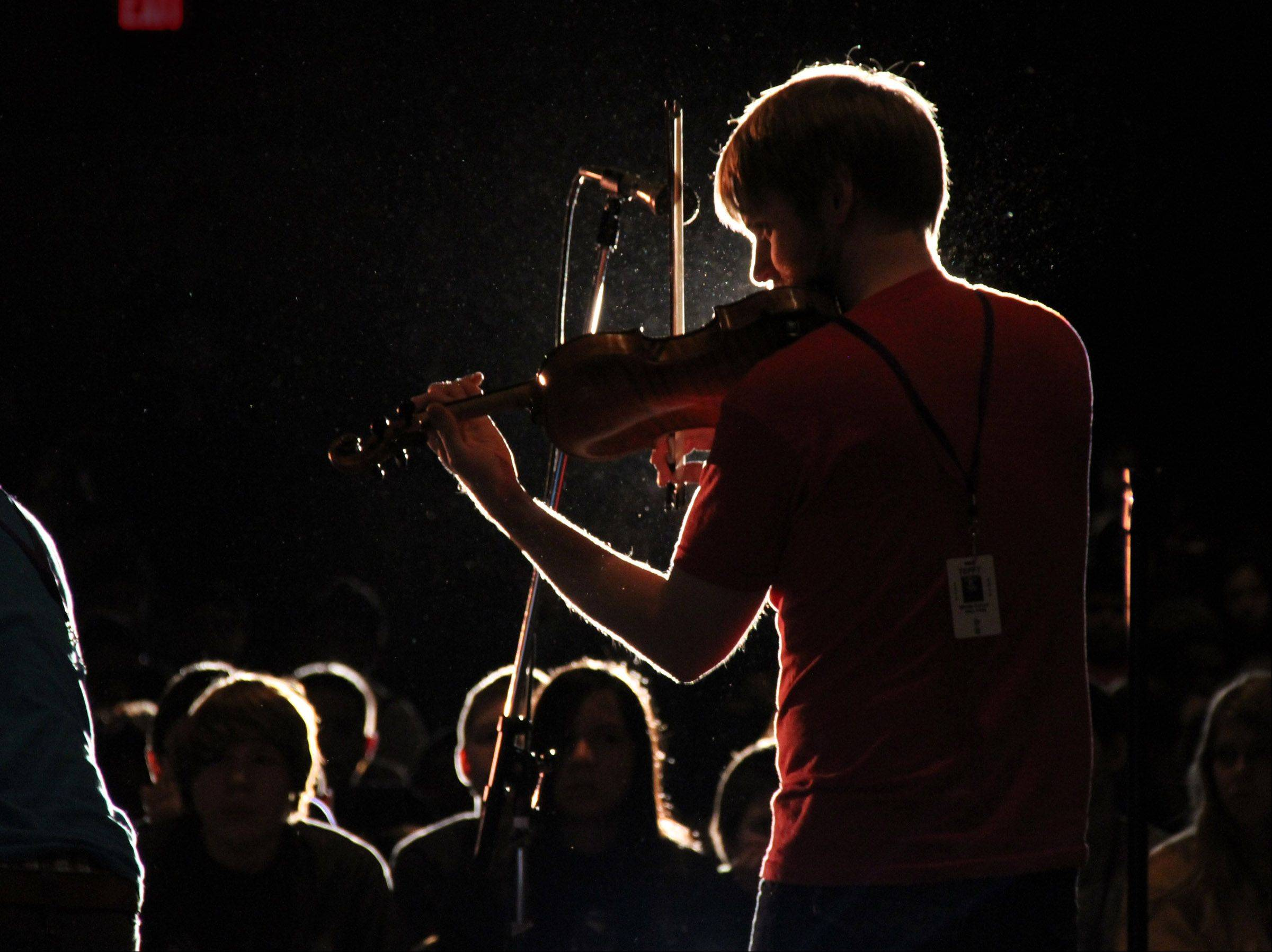 Zach De Pue, with Time for Three, a classically-trained garage band, plays the violin at Tefft Middle School in Streamwood Thursday.
