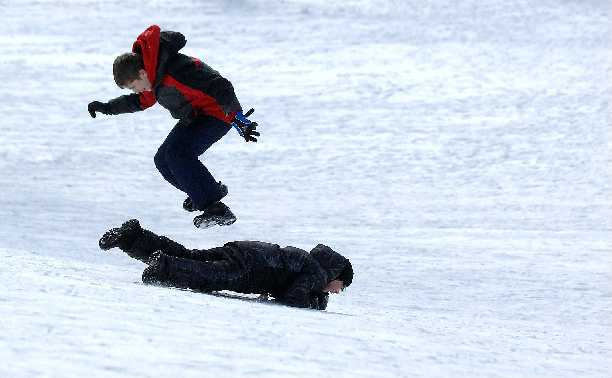 Tony Khouri, 13, of Aurora leaps over friend Will Luetkehans, 12, of DeKalb as he careens down the sledding hill at Fabyan Forest Preserve in Geneva Thursday.