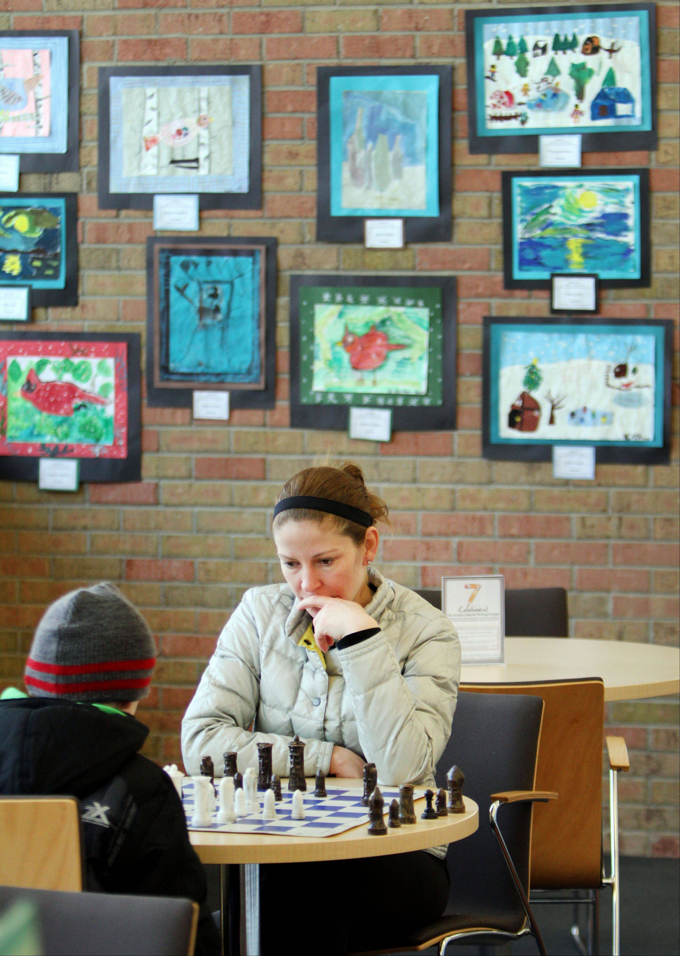 "Jaimie Leighton, of Libertyville, and her 5 year-old son Carson, play chess at Cook Park Library in Libertyville as art projects from District 70 students hang on the wall behind them. The show entitled ""ArtEffects"" will be on display until April 1st."