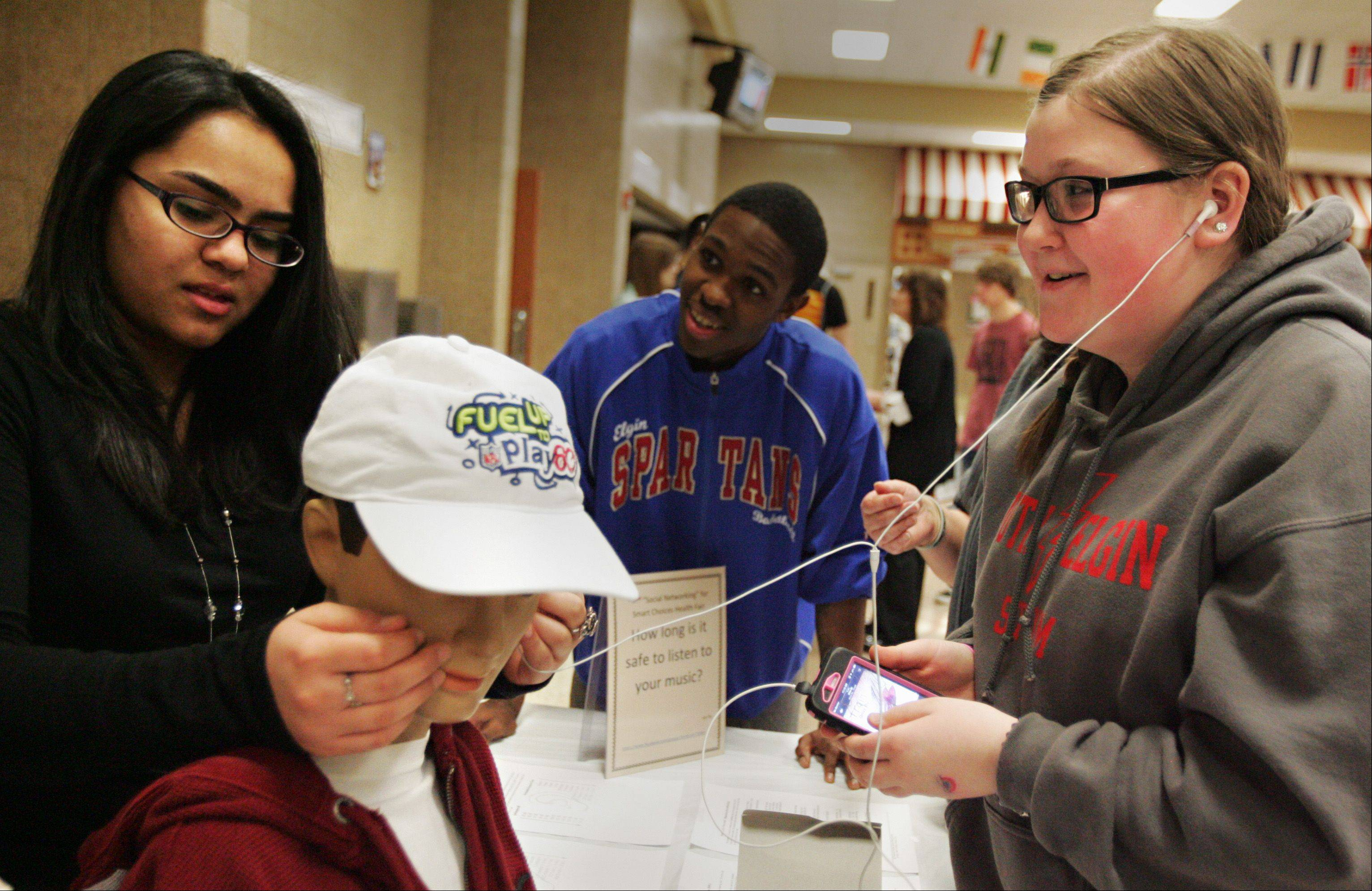 South Elgin High School freshman Gabrielle Lewellyn, right, tests the decibel level on her mp3 player Friday as senior volunteer Nitu Patel looks at a reading on a mannequin during the school's annual health fair. Students could plug their ear buds in a mannequin rigged with a device to detect the decibel level of the sound, and were advised if their music levels could permanently damage their hearing.