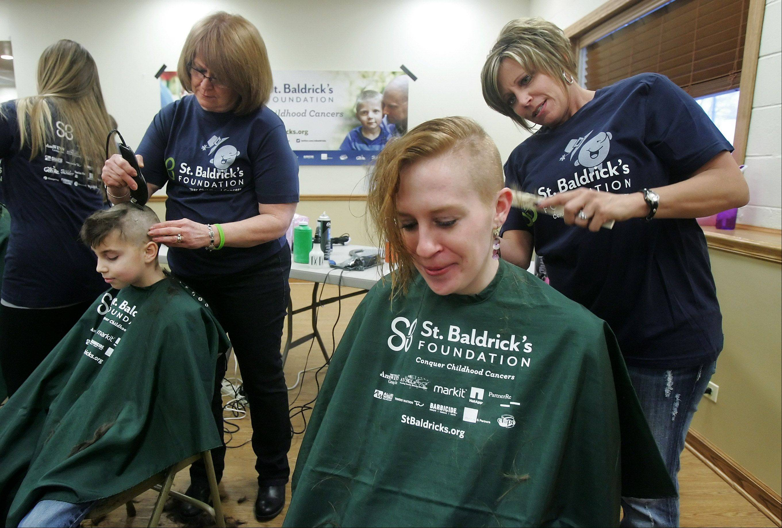 "Lauren Szelewicki, of Ingleside, has her hair cut off by Debbie Kula, of the John Anthony Salon, during the ""Taking It All Off for Cancer Research"" event Sunday at the Fox Lake Volunteer Fire Department. Local firefighters, police and members of the community raised money for the St. Baldrick's fundraiser by having their heads shaved."