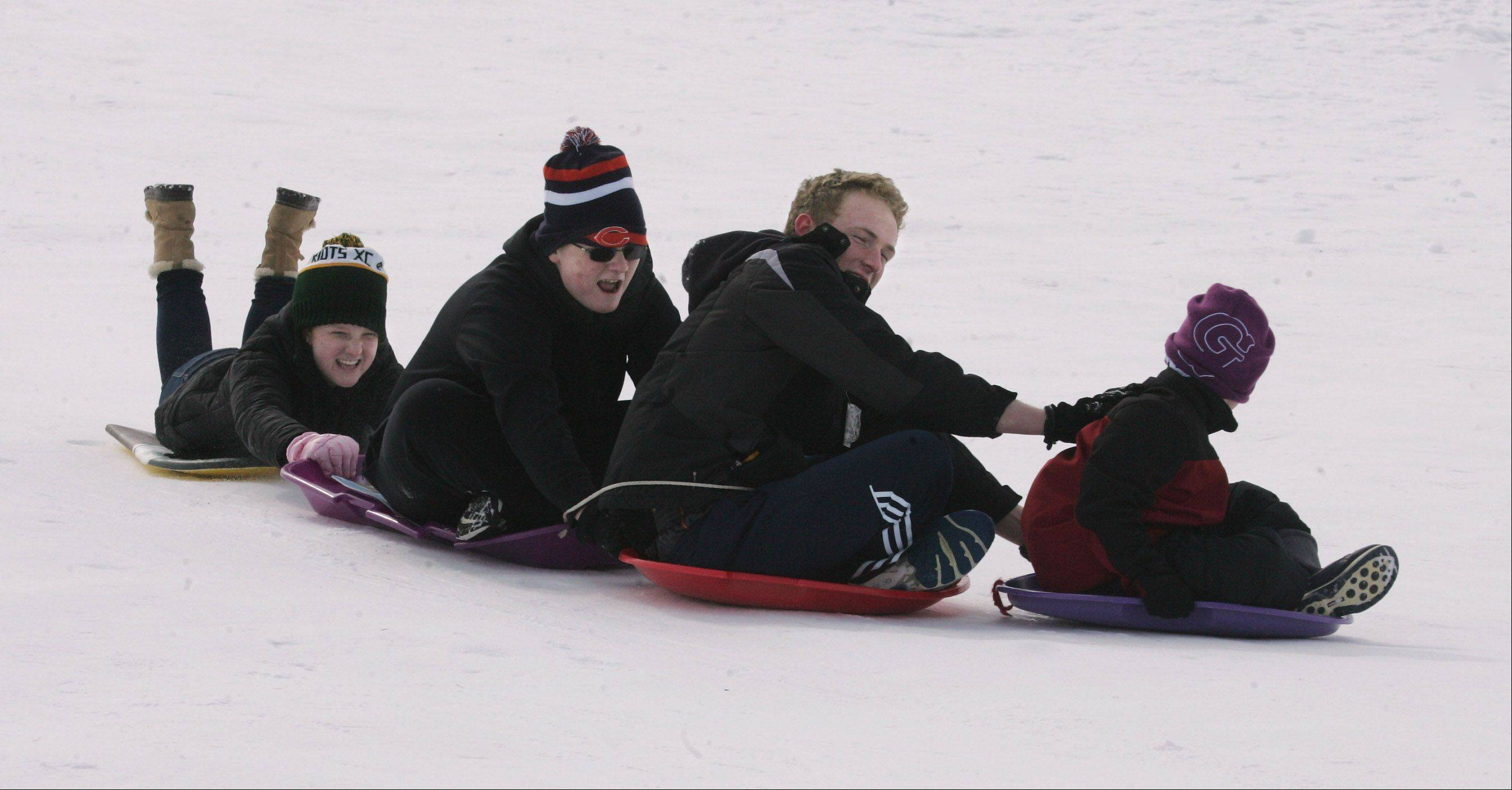 The Jones family of Vernon Hills, including, Dan, right, Hal, Tyler, and Courtney, form a train as they sled doown the hill Monday at Century Park in Vernon Hills.