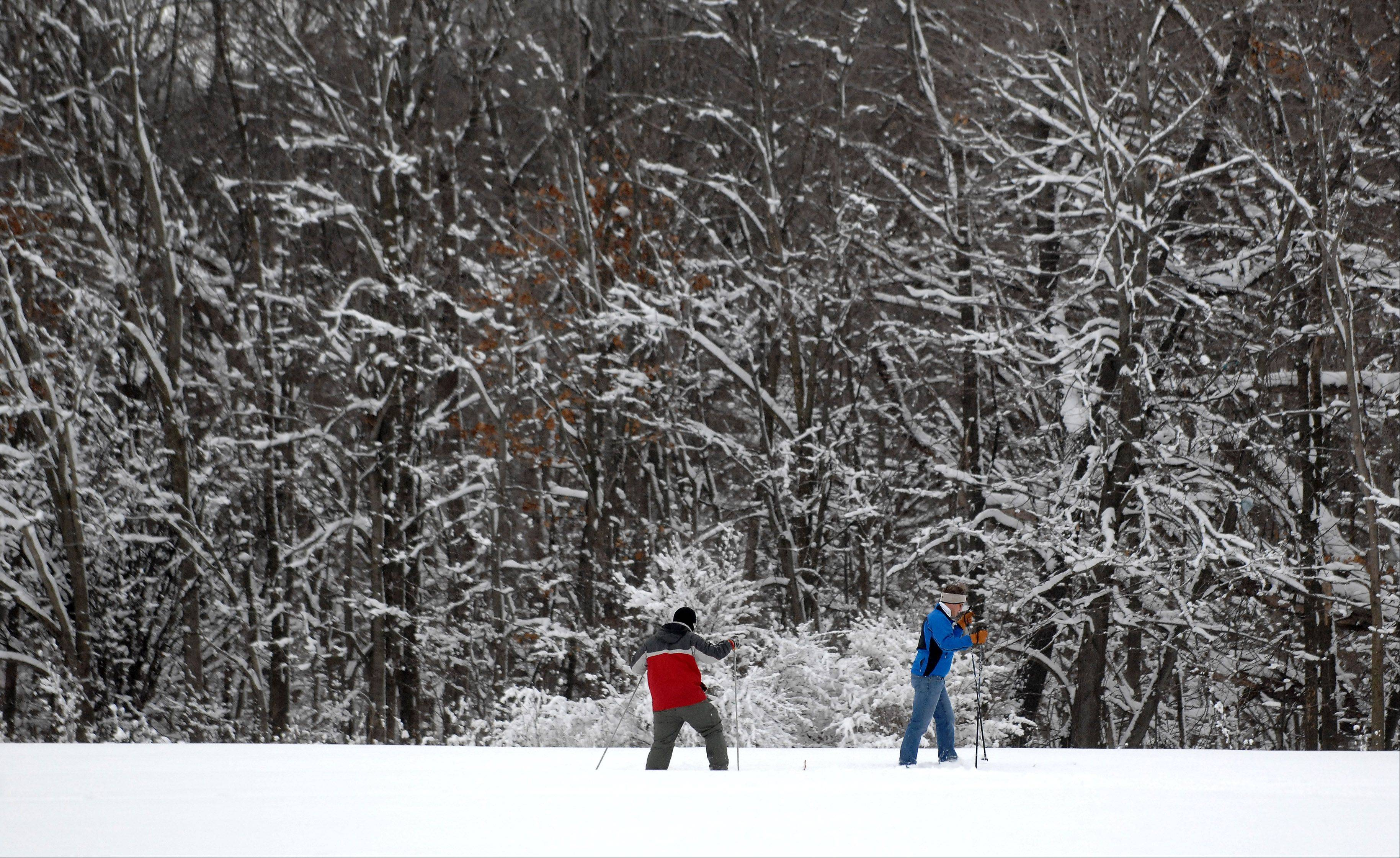 Andrew Kingsley of South Elgin, right, and Scott Kessler of St. Charles, traverse deep snow while cross country skiing through LeRoy Oakes Forest Preserve in St. Charles Wednesday. Kingsley said it was only the second time they'd been out this winter since he prefers cross country skiing when there is more than 10 inches of snow on the ground to avoid scraping up his skis on branches and sticks.