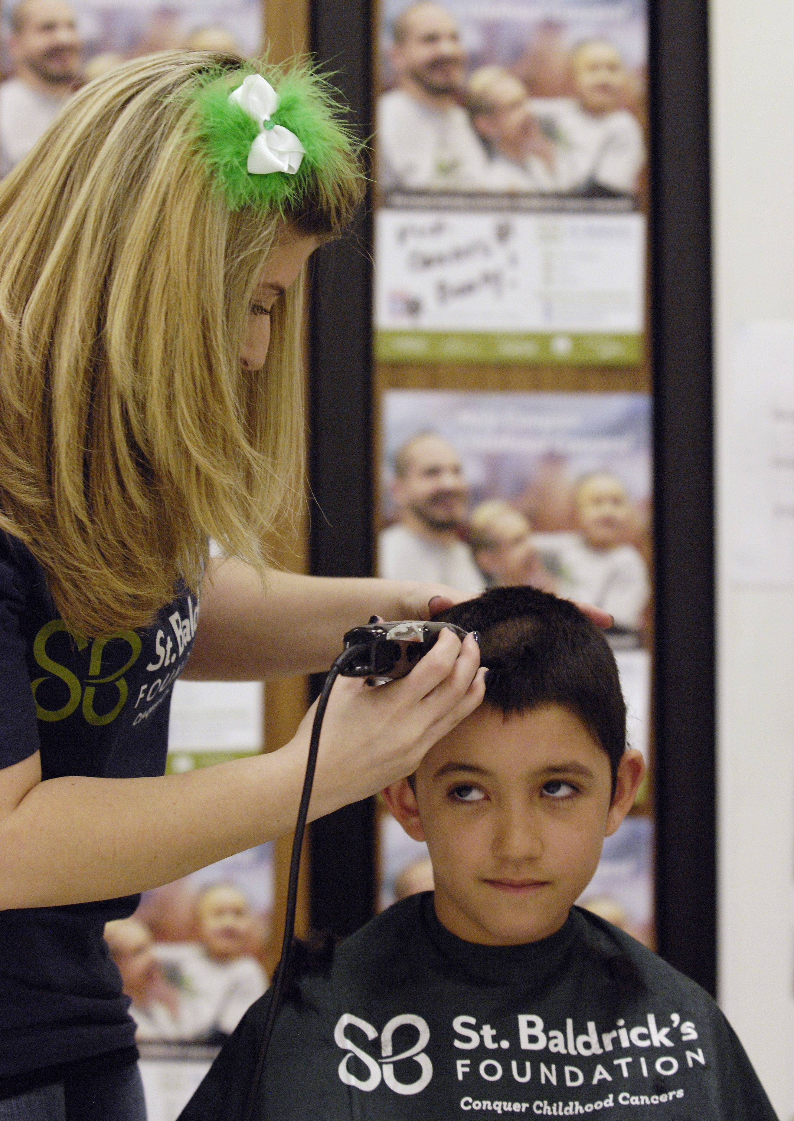 Gina Barzso of Bartlett shaves the head of Enzo Torres, 9 of Aurora during the St. Baldrick's Day head shaving event at Evergreen Elementary School in honor of third grader Jack O'Donoghue, who's cancer is now in remission.