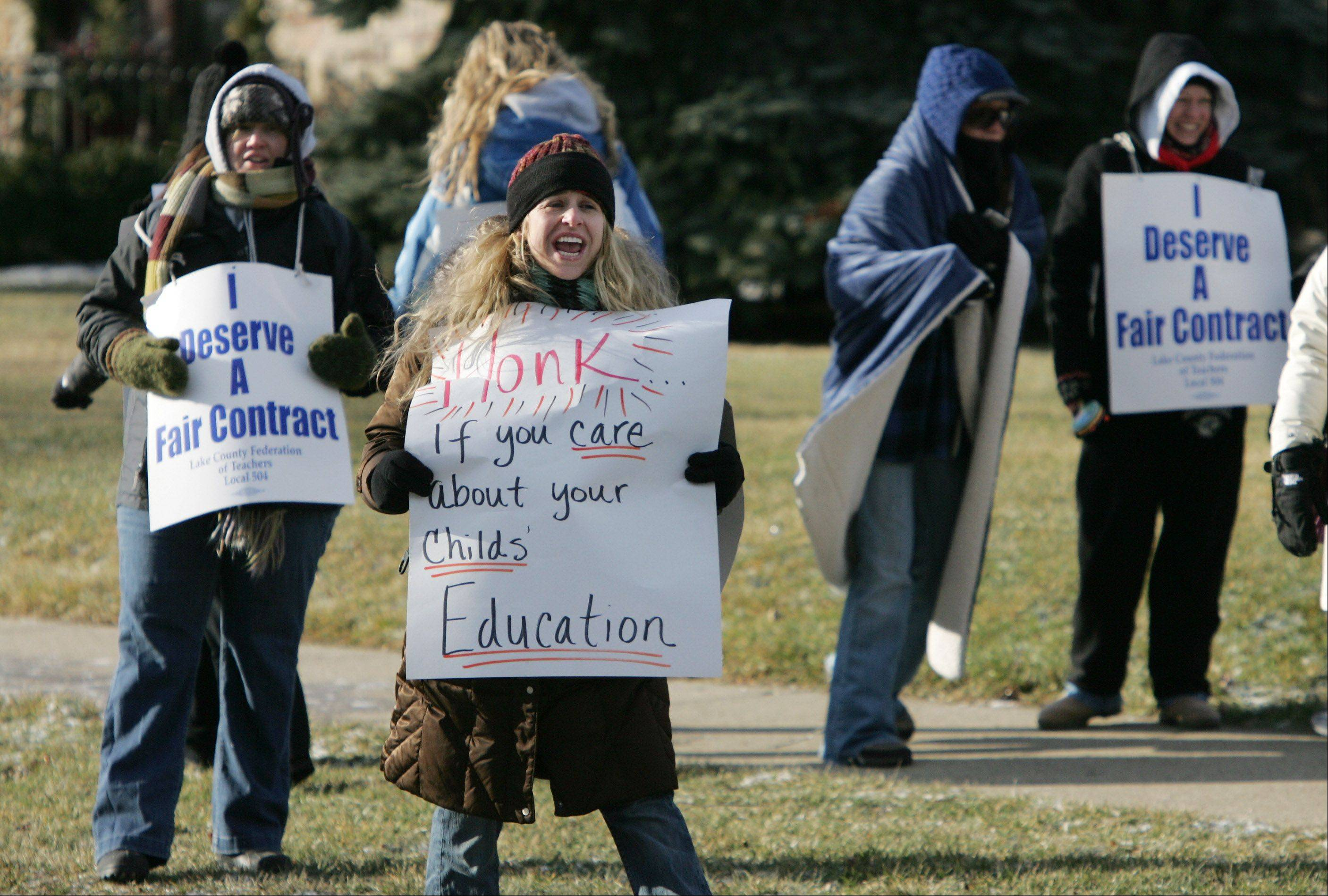 Grayslake Middle School teacher Wendy Chiswick looks for support from passing traffic as Grayslake Elementary School District 46 teachers walk the picket line outside Grayslake Middle School in January.