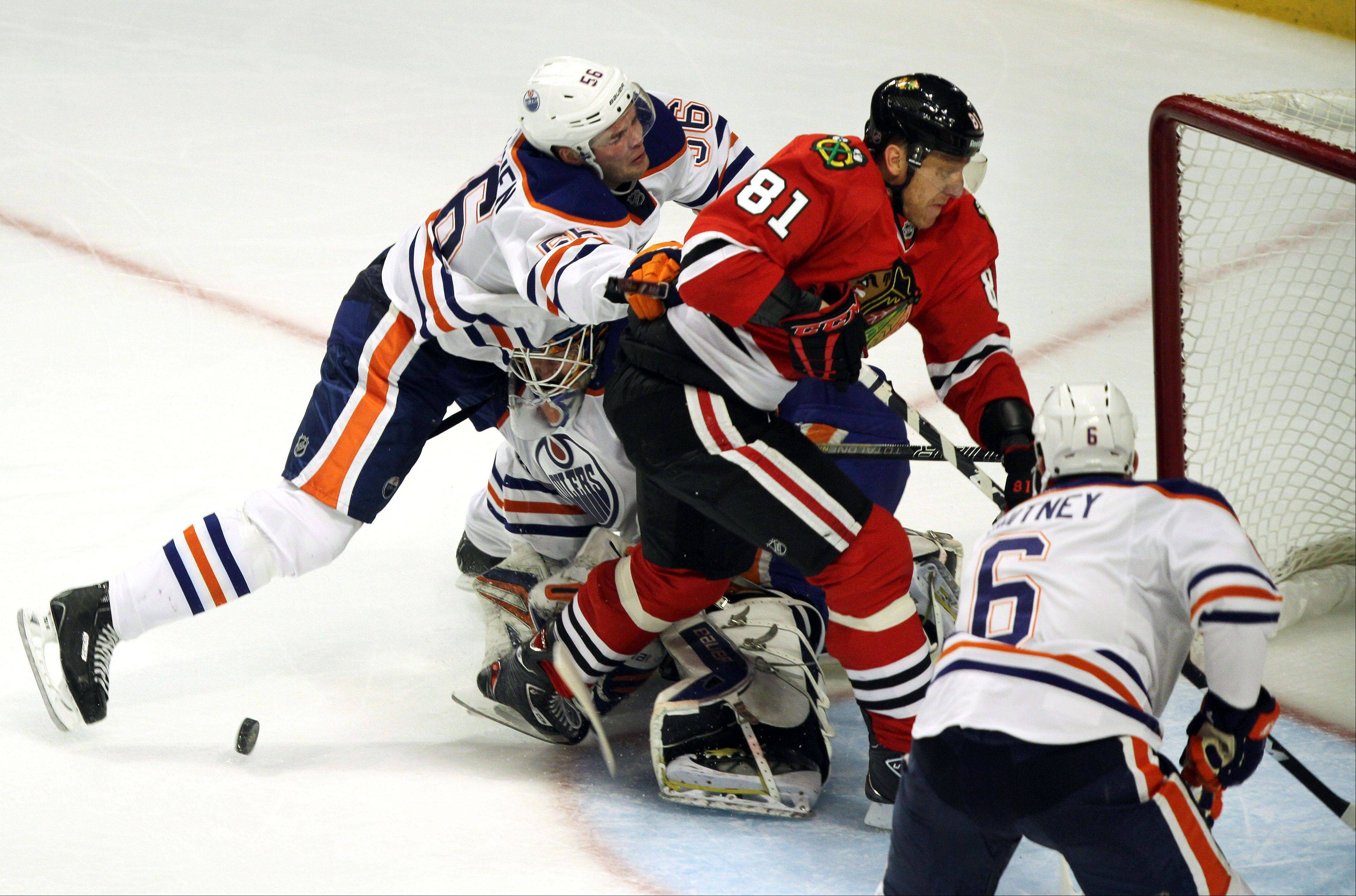 Chicago Blackhawks right wing Marian Hossa runs into Edmonton Oilers goalie Devan Dubnyk during their game Sunday night at the United Center in Chicago.