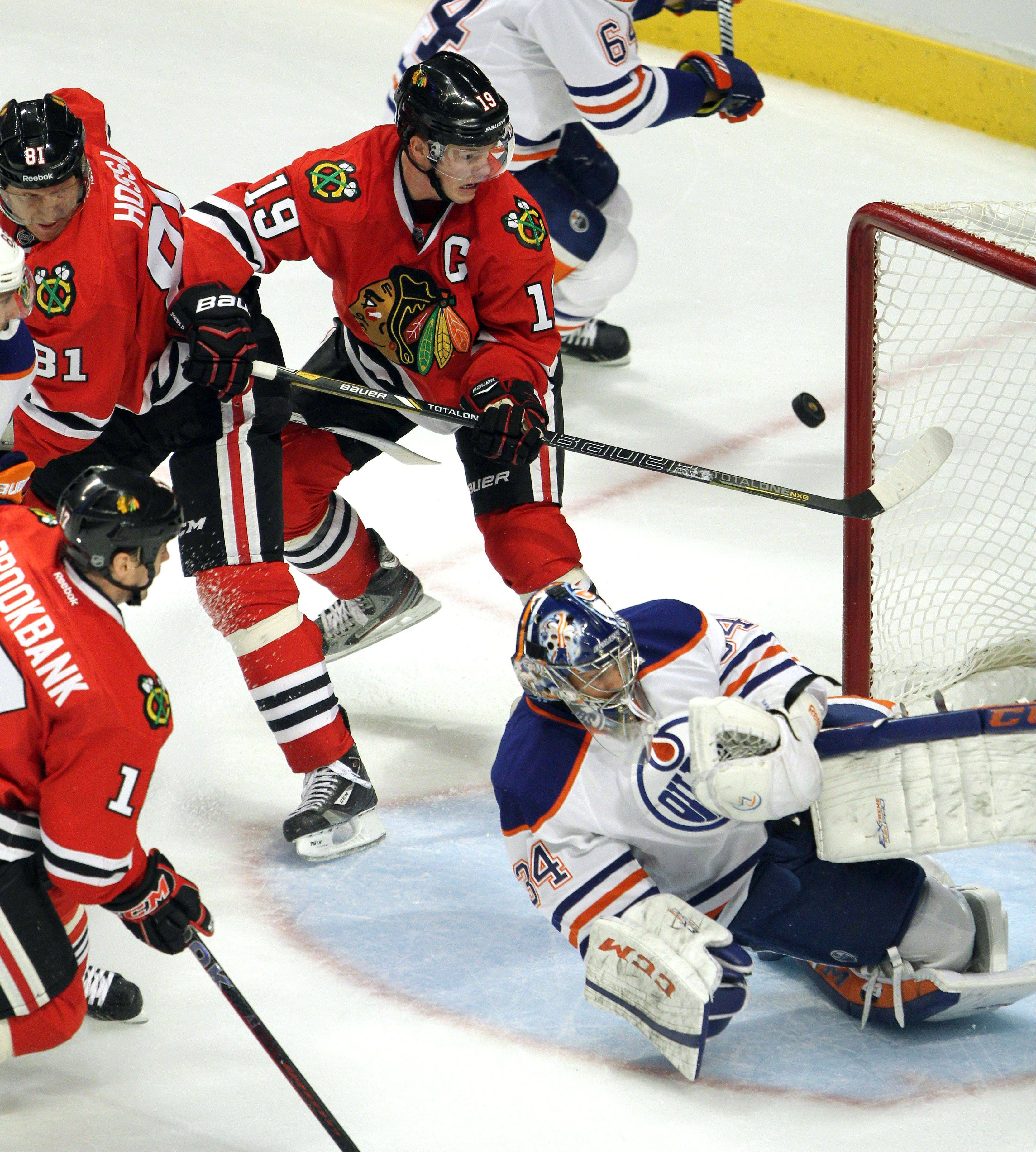 Chicago Blackhawks center Jonathan Toews tries to control a bouncing puck as Edmonton Oilers goalie Yann Danis tries to make the save during their game Sunday night at the United Center in Chicago.