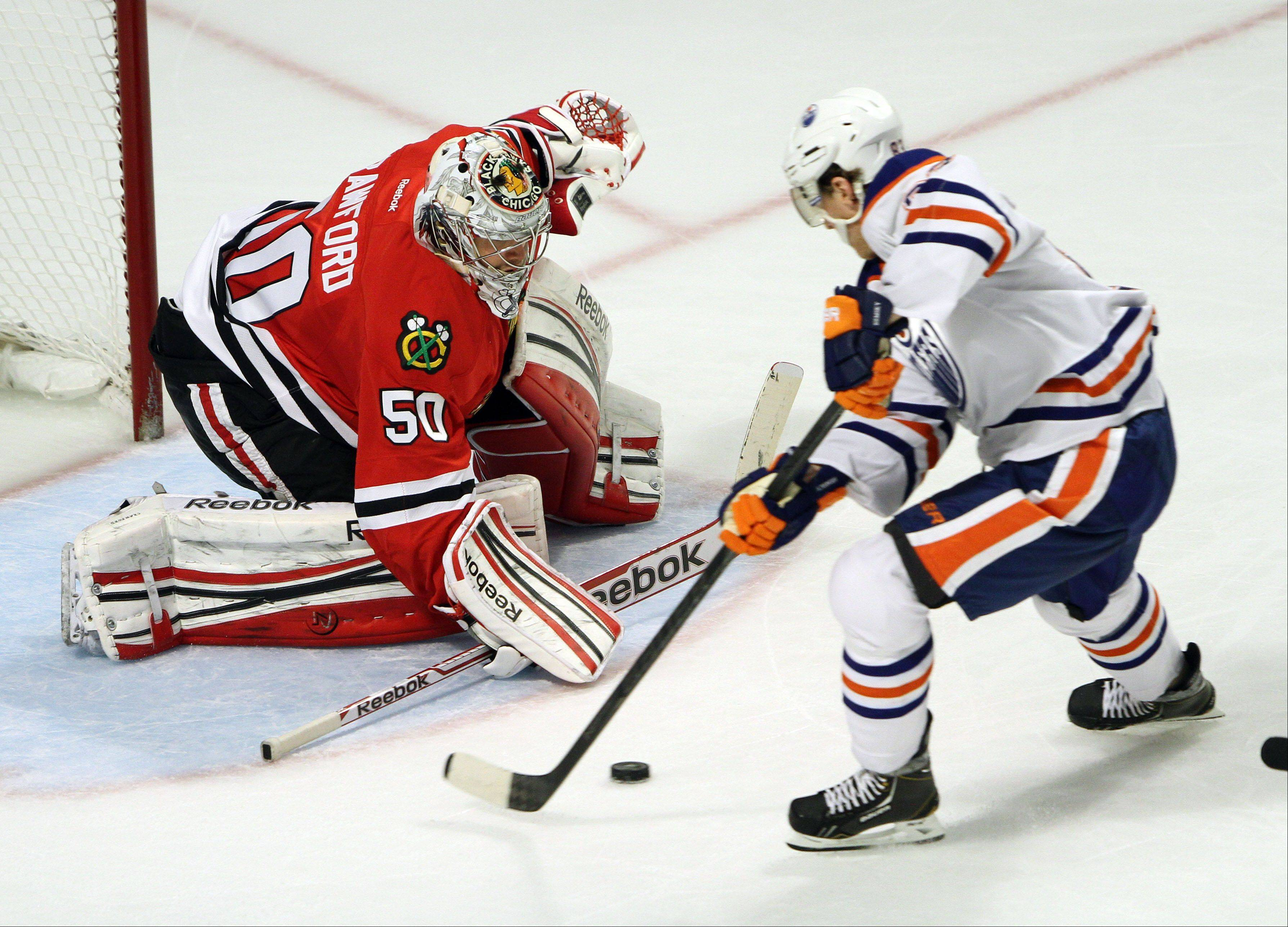 Edmonton Oilers center Shawn Horcoff drives on Chicago Blackhawks goalie Corey Crawford during their game Sunday night at the United Center in Chicago.