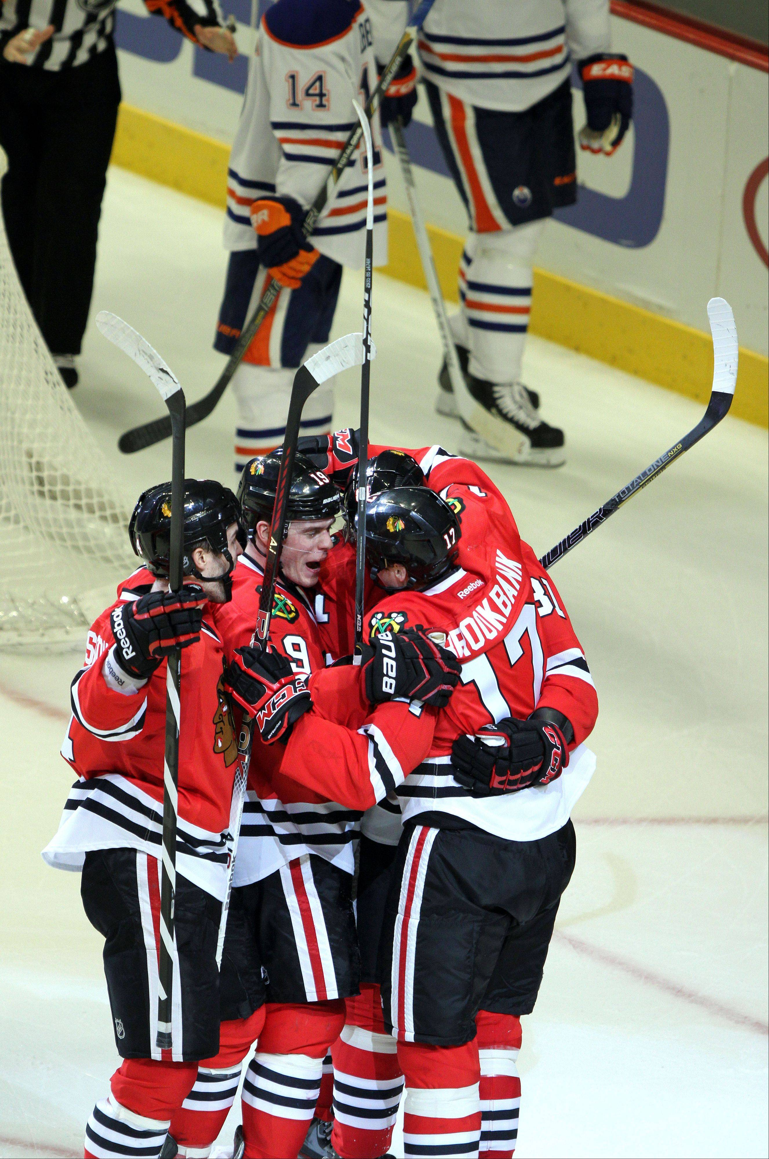 Blackhawks players celebrate with Chicago Blackhawks defenseman Sheldon Brookbank after his second period goal during their game Sunday night at the United Center in Chicago.