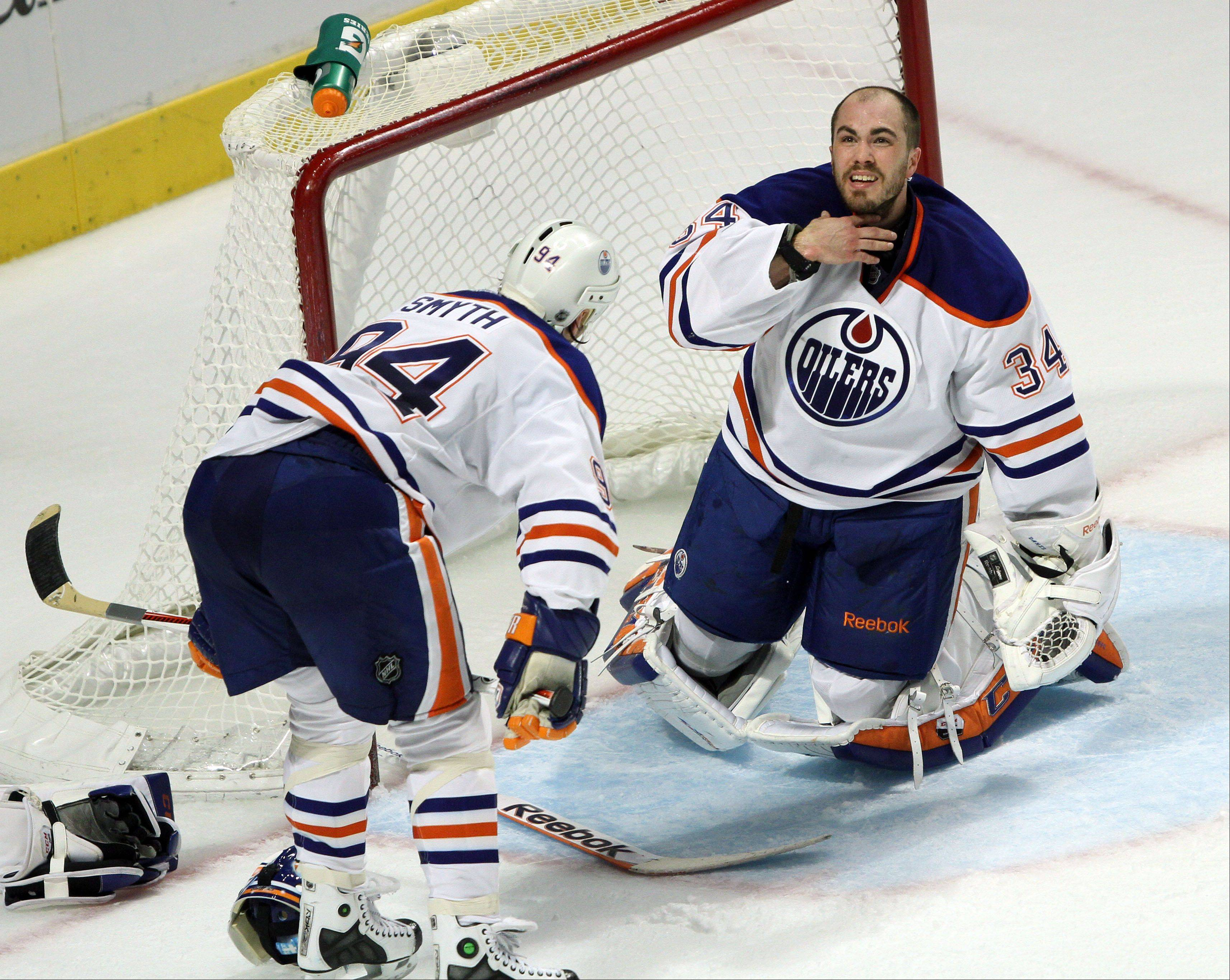 Edmonton Oilers goalie Yann Danis holds his neck after Chicago Blackhawks right wing Marian Hossa collided with him during their game Sunday night at the United Center in Chicago.