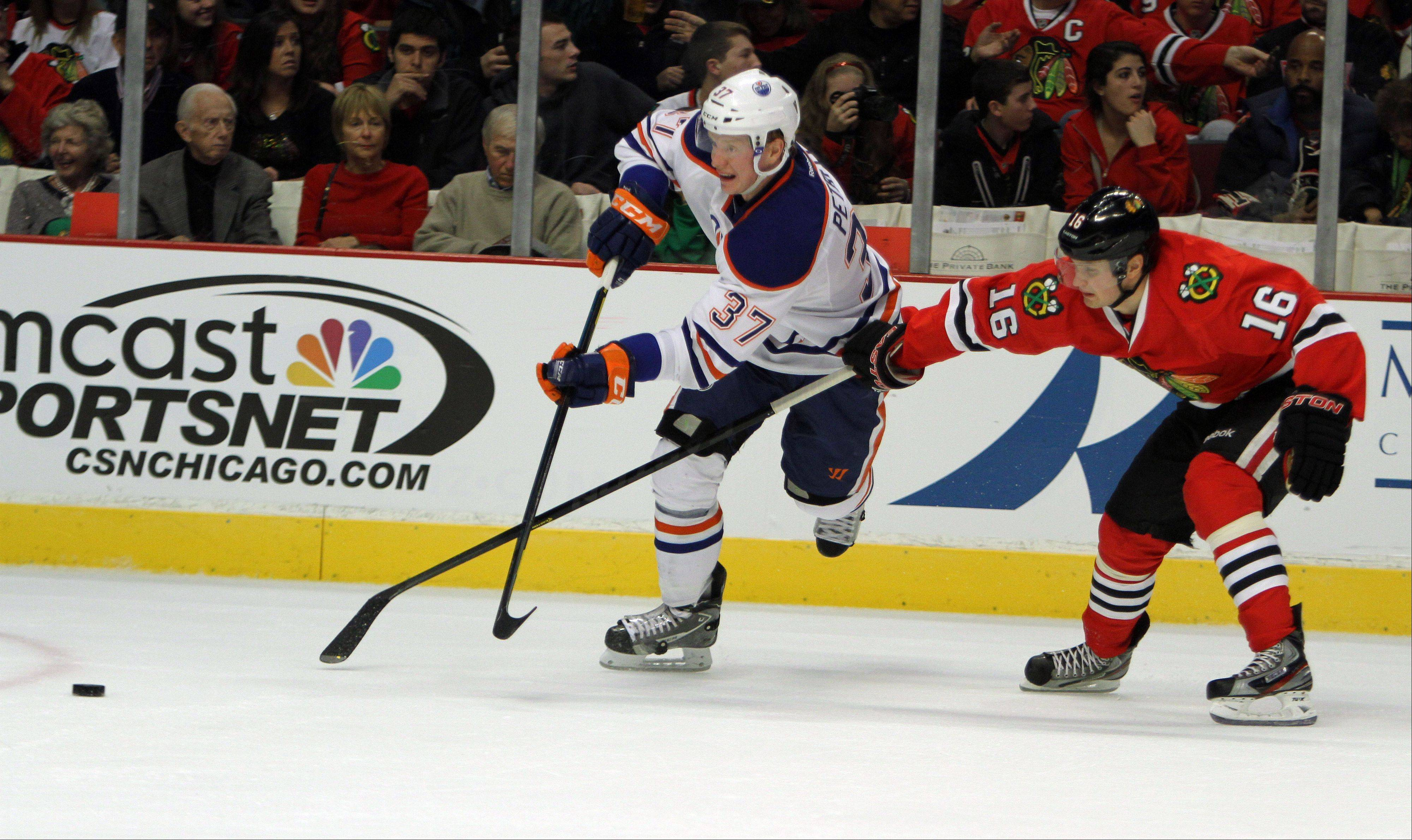 Chicago Blackhawks center Marcus Kruger, right, tries to disrupt Edmonton Oilers center Lennart Petrell during their game Sunday night at the United Center in Chicago.