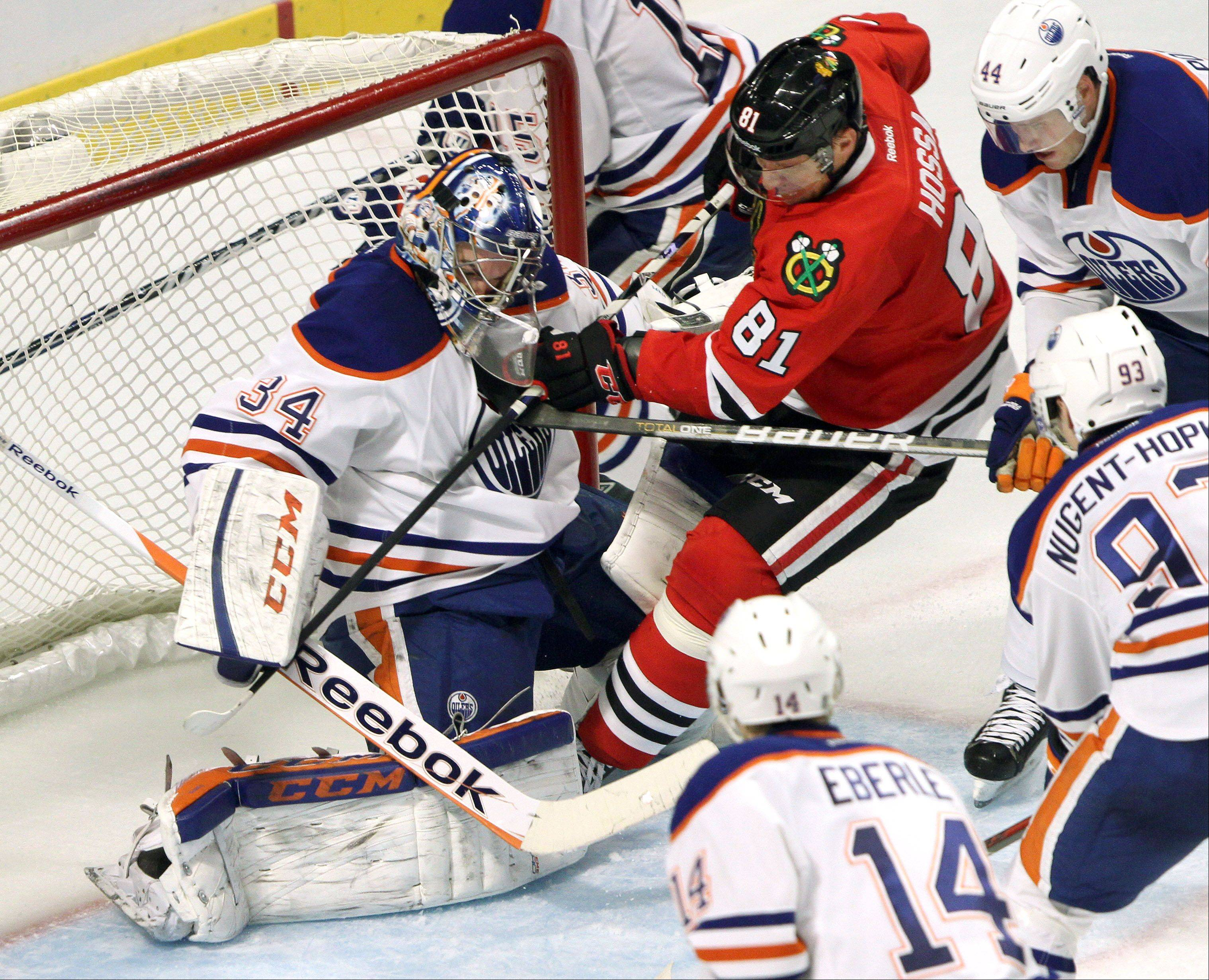 Chicago Blackhawks right wing Marian Hossa collides with Edmonton Oilers goalie Yann Danis during their game Sunday night at the United Center in Chicago.