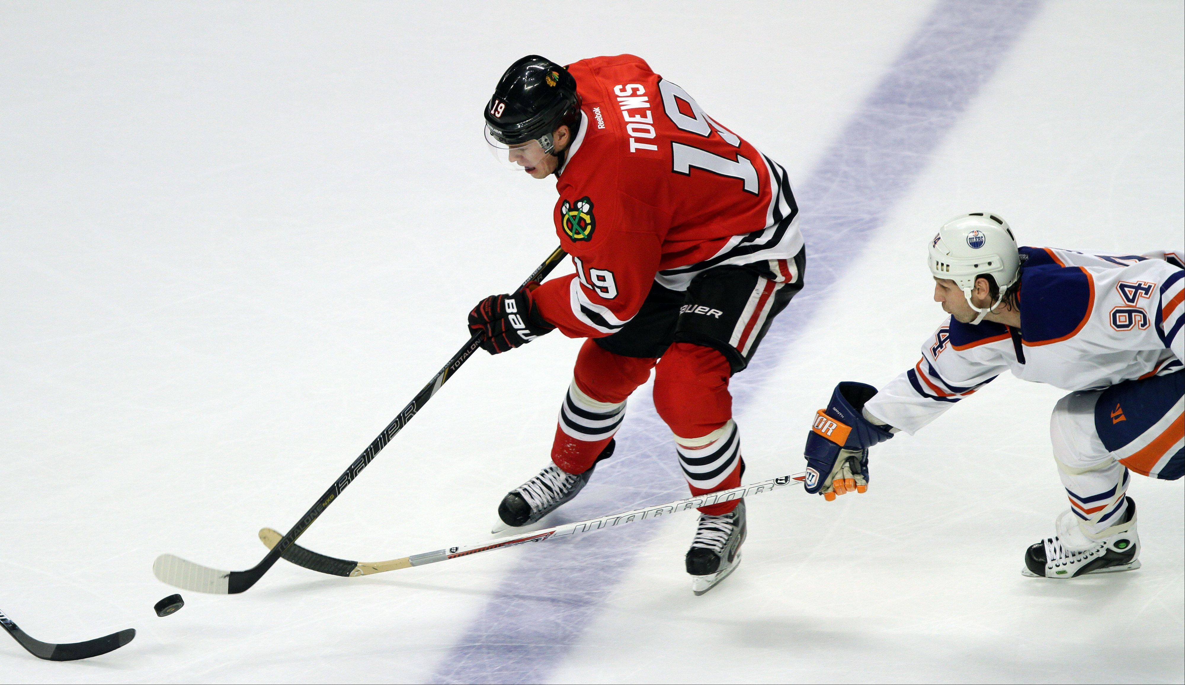 Chicago Blackhawks center Jonathan Toews drives on Edmonton Oilers left wing Ryan Smyth during their game Sunday night at the United Center in Chicago.