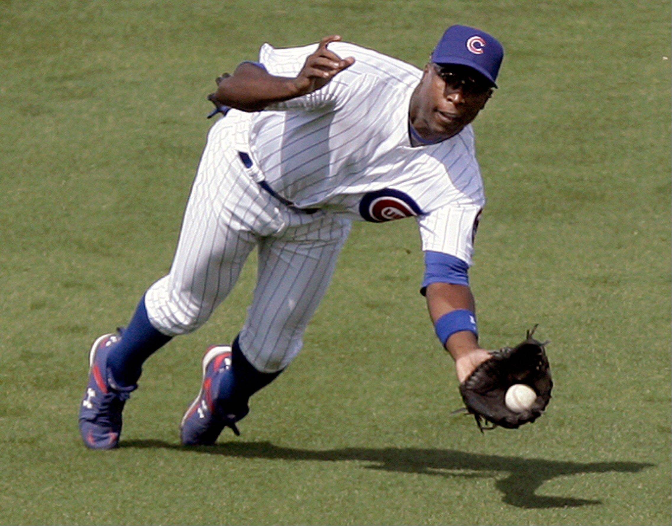 Cubs left fielder Alfonso Soriano lunges to make a catch on a fly ball hit by Chicago White Sox batter Omar Visquel in the second inning of an MLB spring training baseball game Saturday, March 6, 2010, in Mesa, Ariz.