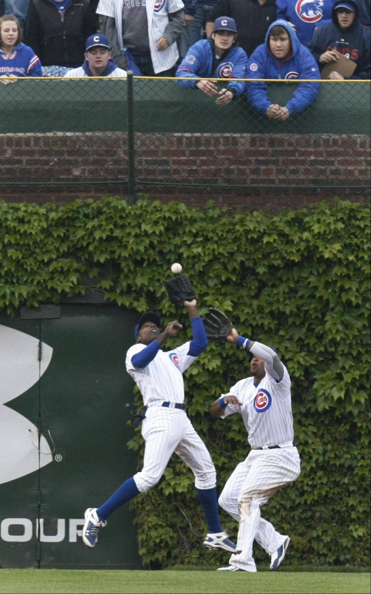 Cubs left fielder Alfonso Soriano, left, leaps in front of center fielder Marlon Byrd to catch a long fly ball by Florida Marlins' Ronny Paulino to end the top half of the sixth inning of a baseball game Wednesday, May 12, 2010 at Wrigley Field in Chicago.
