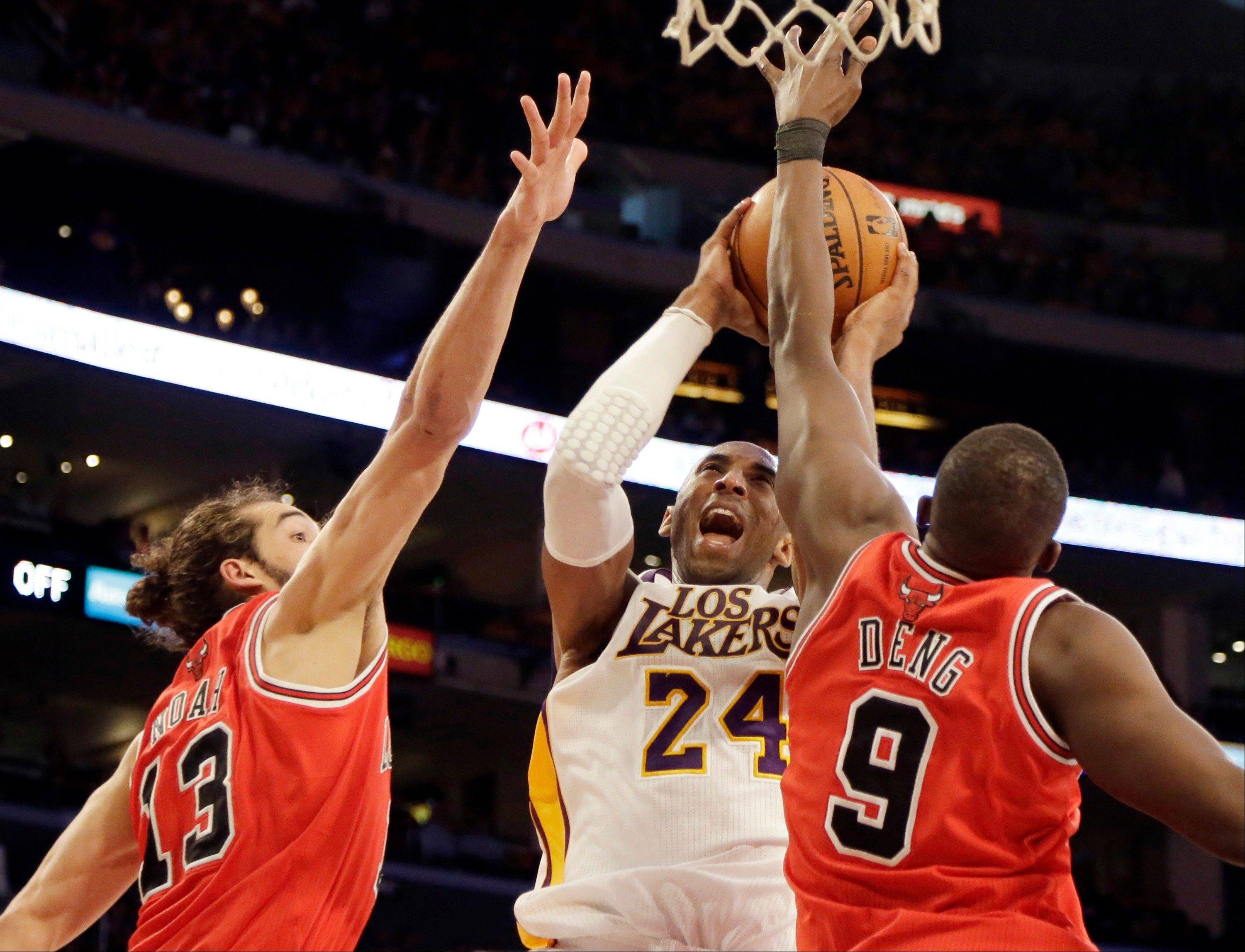 Los Angeles Lakers guard Kobe Bryant shoots as he is defended by Chicago Bulls center Joakim Noah and forward Luol Deng in the first half of an NBA basketball game in Los Angeles Sunday, March 10, 2013.