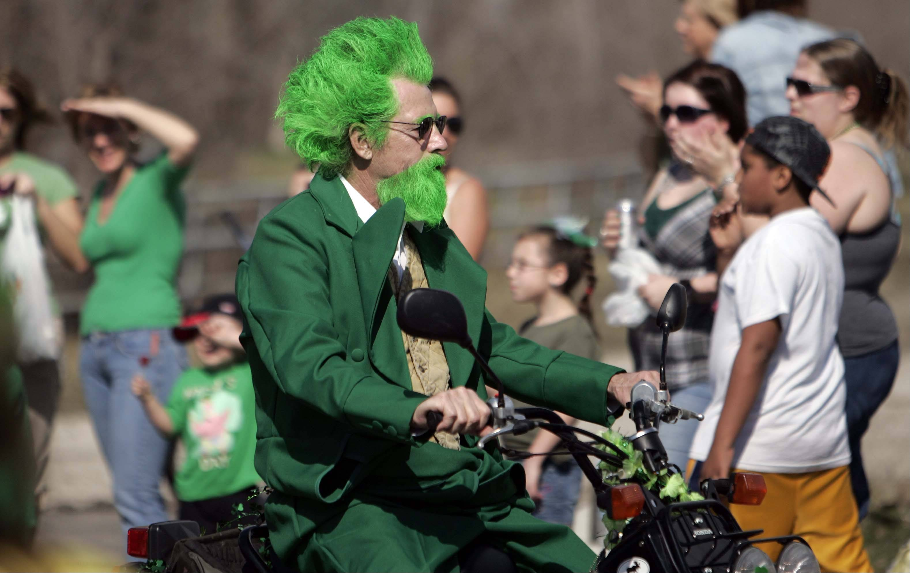 With a green suit to match his bright green hair, Kevin Combest rides through the Thom McNamee Memorial St. Patrick�s Day Parade in East Dundee last year. This year�s parade is Saturday, March 16.
