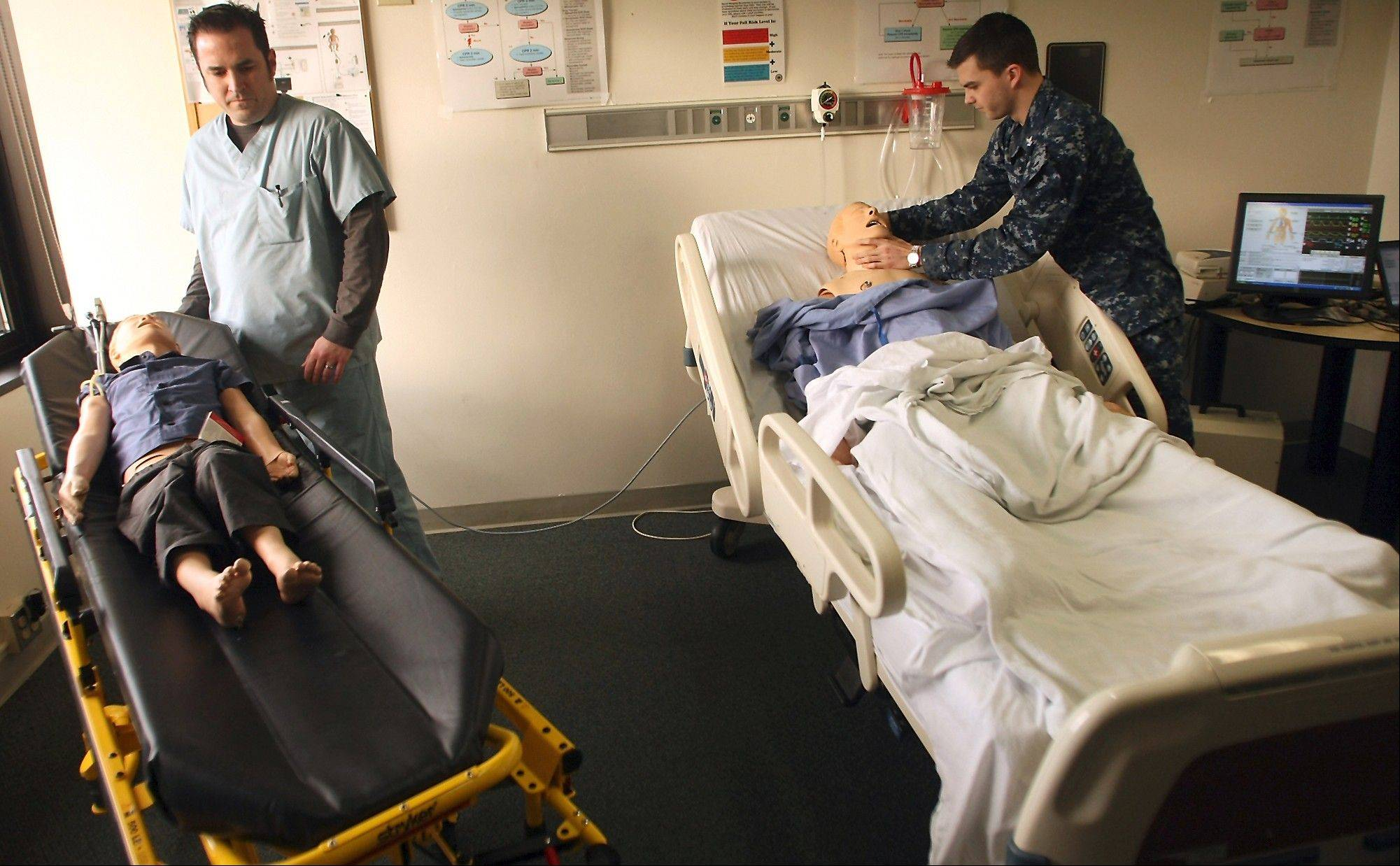 Simulator operator Doug Jones, left, and Corpsman 2nd Class Blake Hite, right, get a pair of patient simulators ready for students at the Naval Hospital Bremerton.