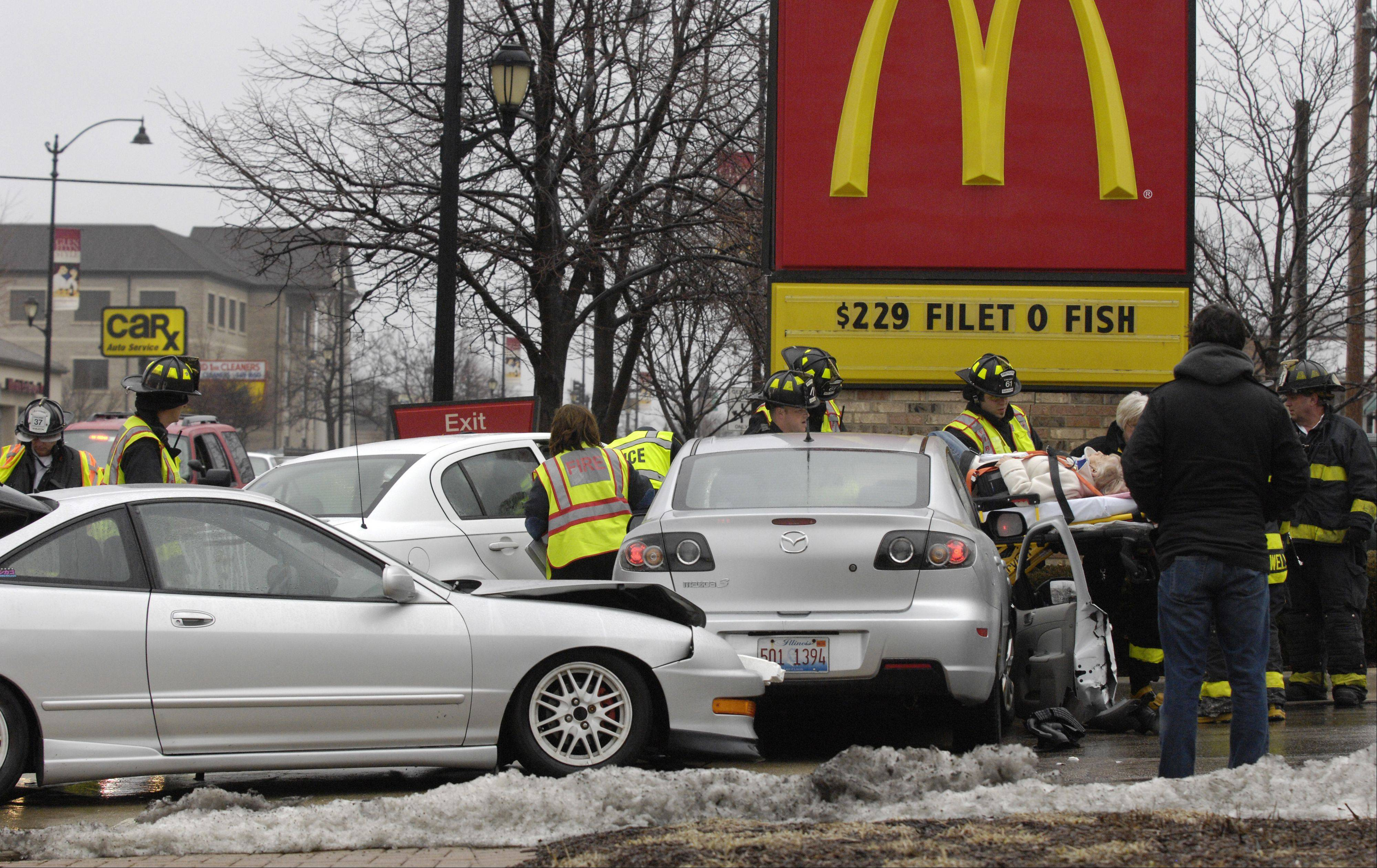 Glen Ellyn firefighters and police officers work the scene of a three-car accident Monday afternoon at the entrance of the McDonald's on Roosevelt Road.