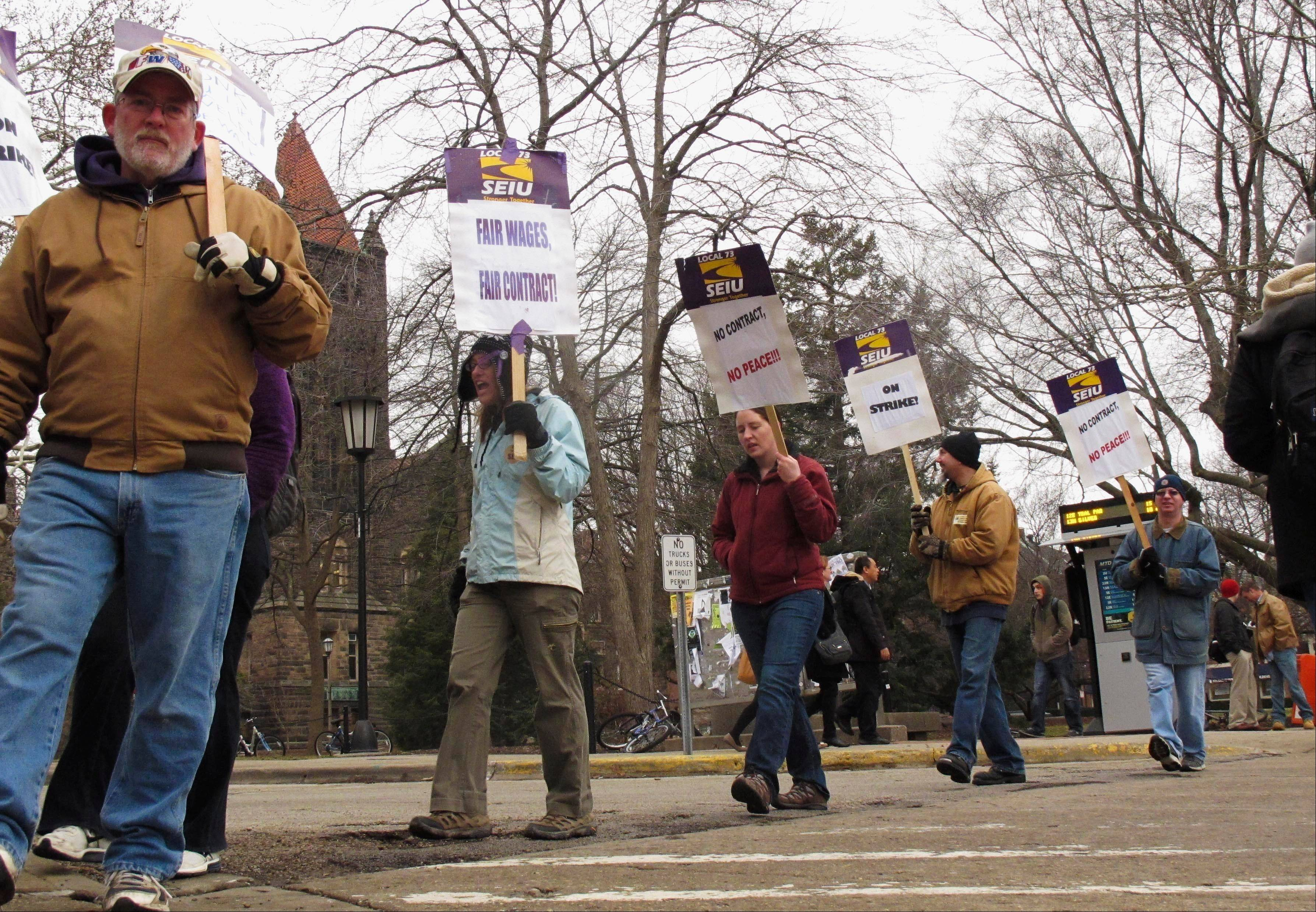 John Hill, left, and other members of the Service Employees International Union at the University of Illinois walk a picket line Monday outside the Illini Union in Urbana.