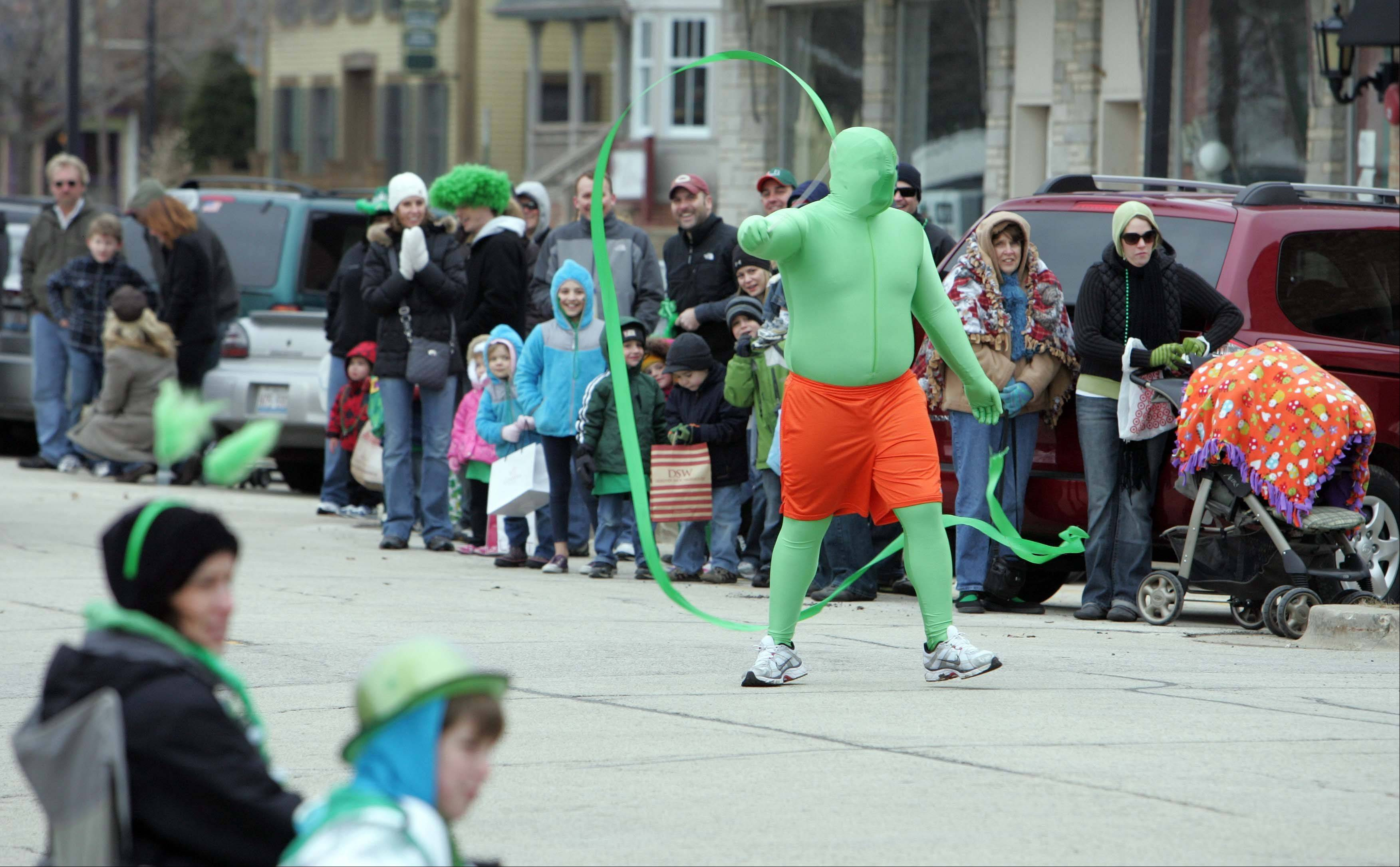 A man dressed in green performs for the crowd during the 2011 Thom McNamee Memorial St. Patrick's Day Parade in East Dundee.