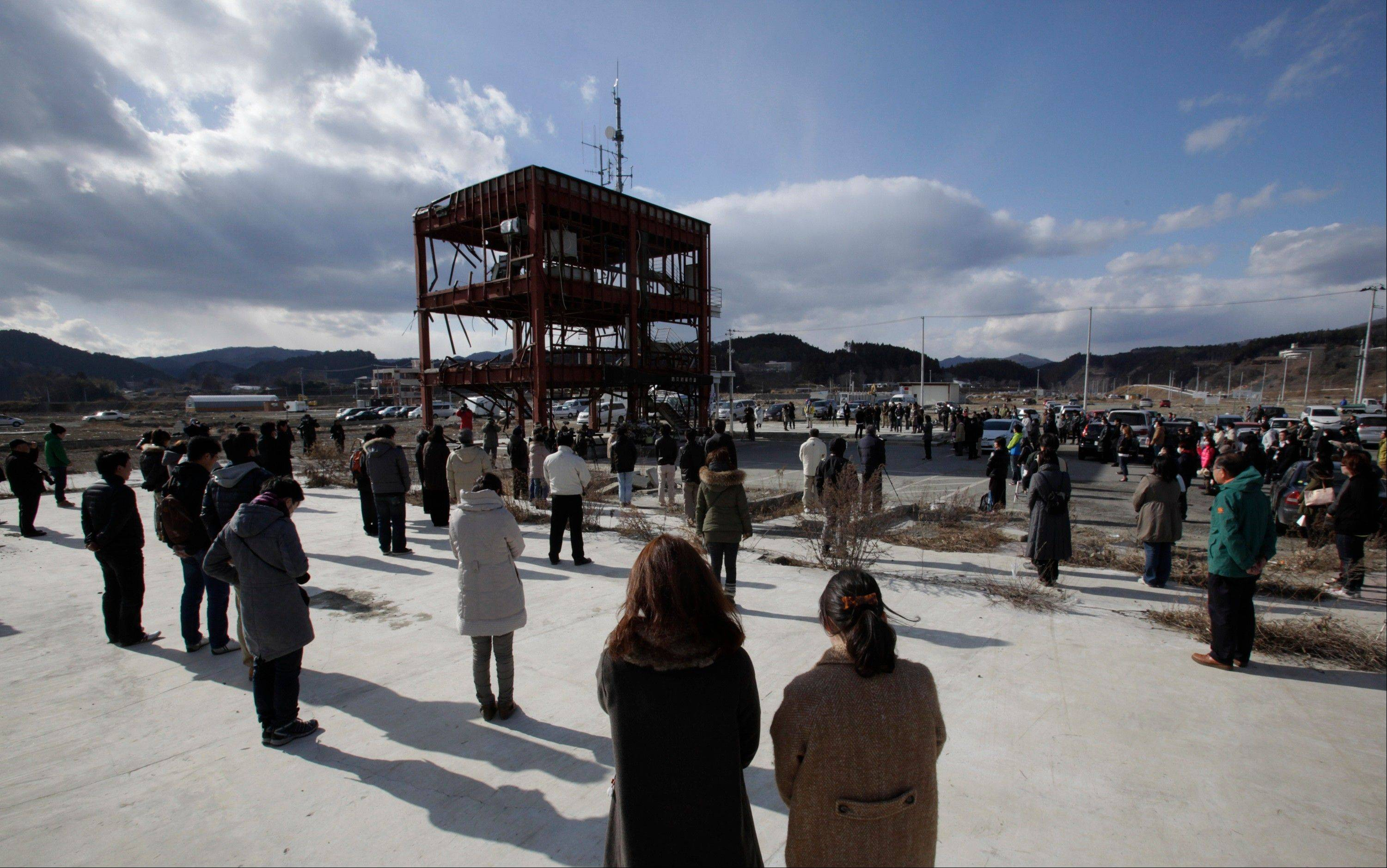 Gathering around what is left of a disaster control center devastated by the March 11, 2011 earthquake and tsunami, people bow their heads Monday, March 11, 2013 in Minamisanriku, Miyagi prefecture, Japan, in a moment of silence at 2:46 p.m. when the magnitude 9.0 earthquake struck off Japan's northeastern coast. Japan marked the second anniversary on Monday of a devastating disasters that left nearly 19,000 people dead or missing.