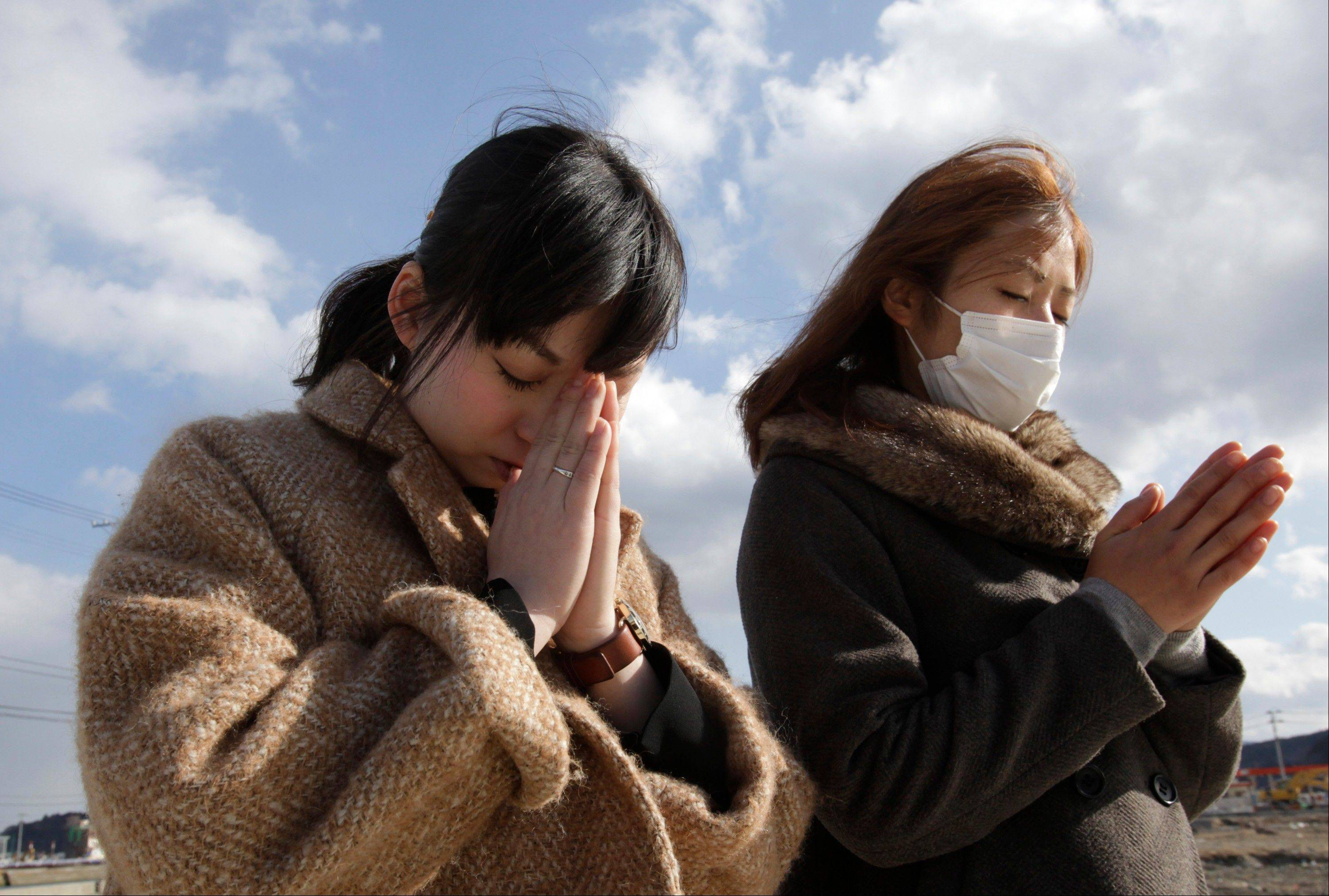 People offer prayer in a moment of silence in front of what is left of a disaster control center in an area devastated by the March 11, 2011 earthquake and tsunami in Minamisanriku, Miyagi Prefecture, Monday, March 11, 2013. Japan marked the second anniversary on Monday of the devastating disasters that left nearly 19,000 people dead or missing.