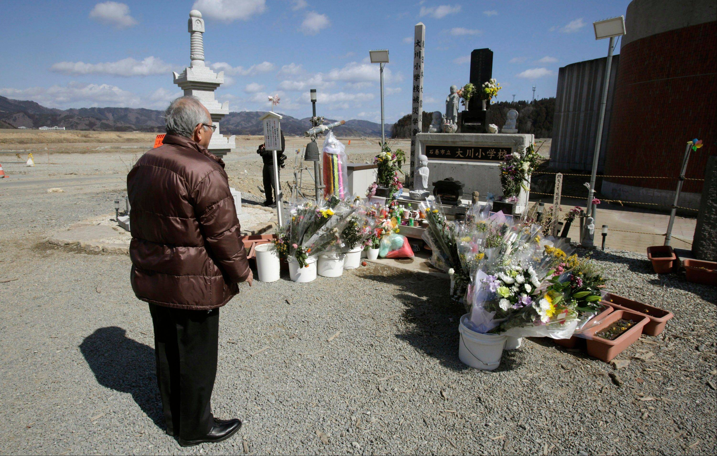 A man offers prayers in front of the main entrance of Okawa Elementary School where 74 of the 108 students went missing after the March 11 tsunami in Ishinomaki, Miyagi prefecture, Japan, Monday, March 11, 2013. The two-year anniversary Monday of Japan's devastating earthquake, tsunami and nuclear catastrophe is serving to spotlight the stakes of the country's struggles to clean up radiation, rebuild lost communities and determine new energy and economic strategies.