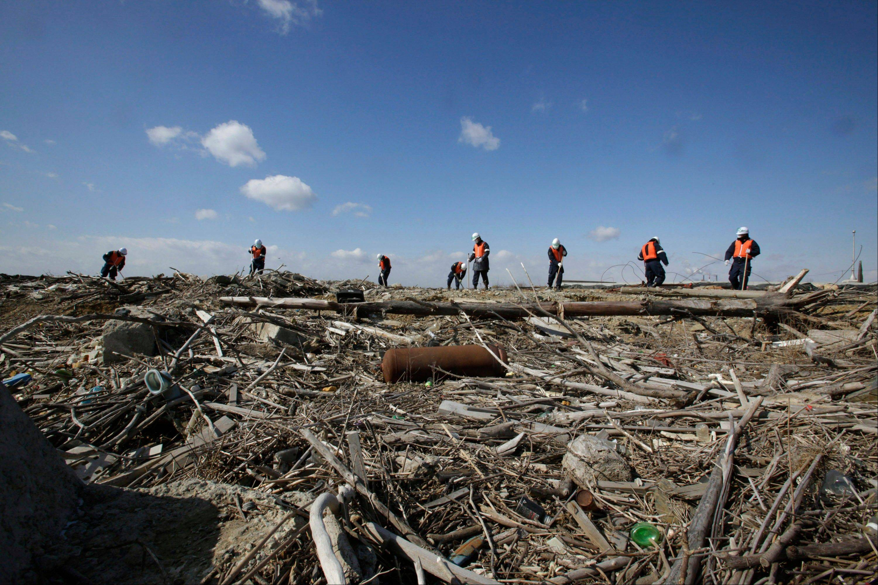 Police officers search for the remains of those who went missing in the March 11, 2011 tsunami on the coastline in Ishinomaki, Miyagi Prefecture, northern Japan, Monday, March 11, 2013. The two-year anniversary Monday of Japan's devastating earthquake, tsunami and nuclear catastrophe is serving to spotlight the stakes of the country's struggles to clean up radiation, rebuild lost communities and determine new energy and economic strategies.