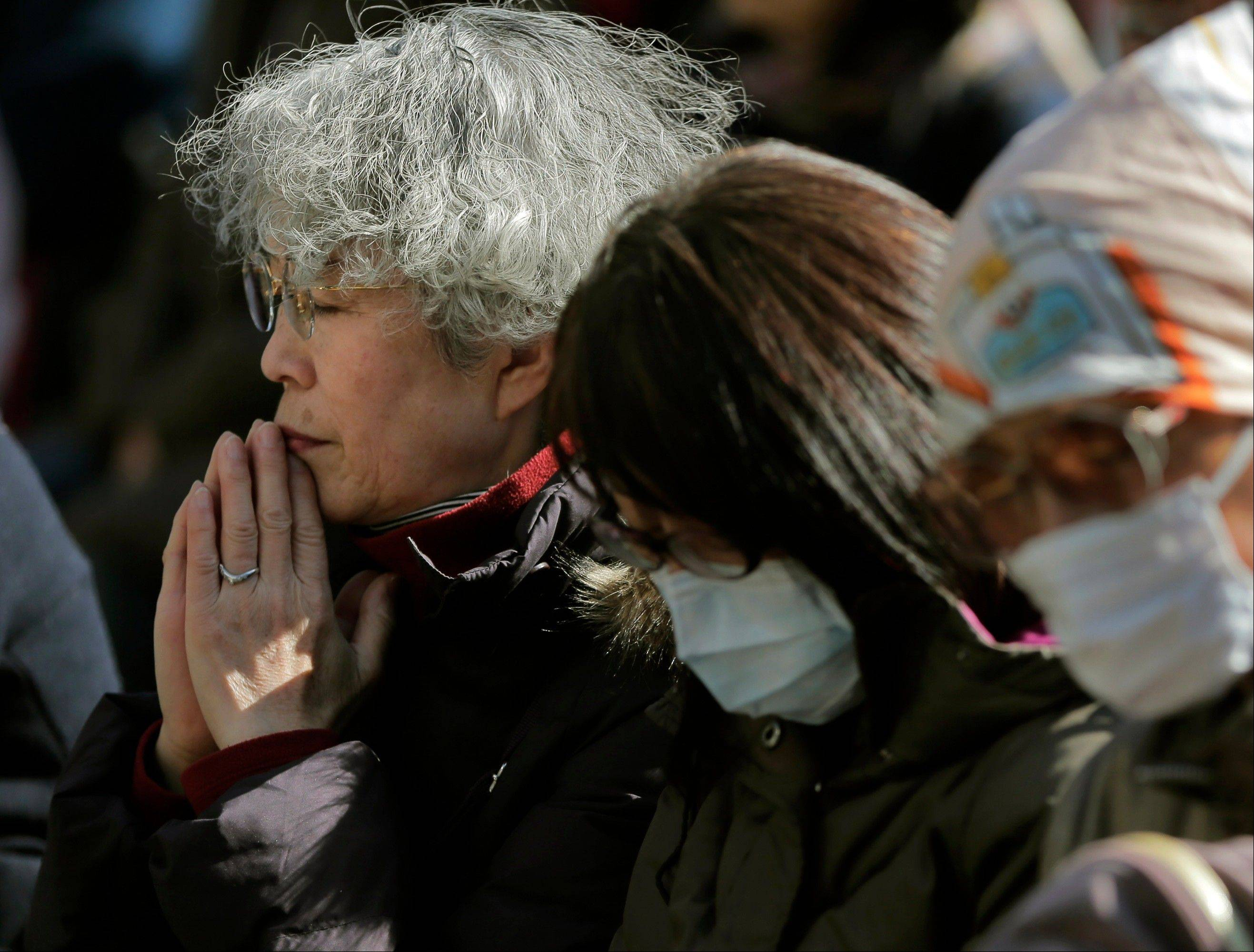 People observe a moment of silence for the victims of the March 11, 2011 earthquake and tsunami during an event at a park in Tokyo, Monday, March 11, 2013. Japan marked the second anniversary on Monday of a devastating earthquake and tsunami that left nearly 19,000 people dead or missing.