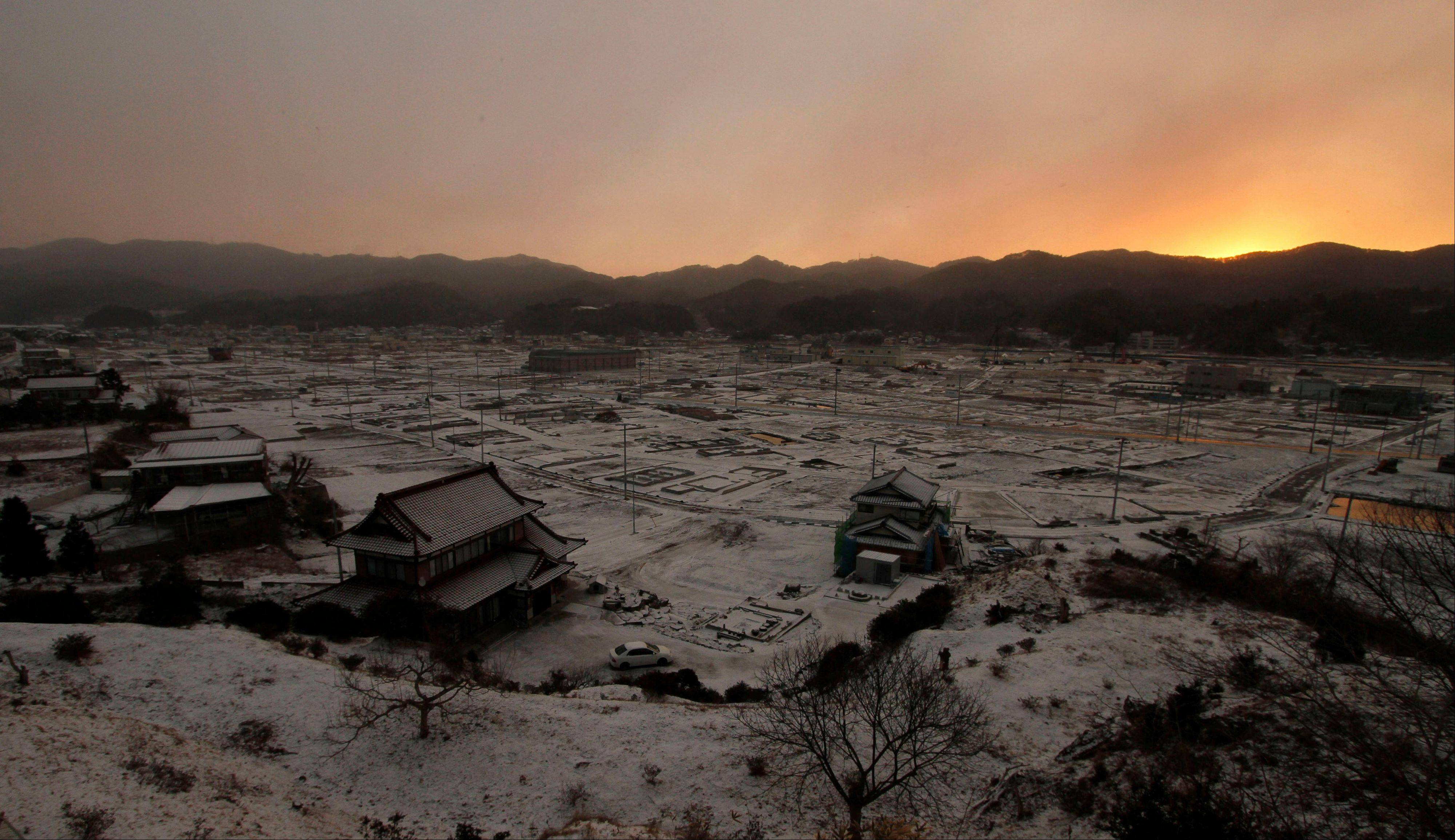 Houses stand on a snow covered deserted port area, which was engulfed by a tsunami after the March 11, 2011 earthquake, in Kesennuma, Miyagi Prefecture, northeastern Japan, at dawn on Monday, March 11, 2013. Japan is marking the second anniversary of its earthquake, tsunami and nuclear catastrophe. Memorial services are planned Monday in Tokyo and in barren towns along the battered northeastern coast to coincide the moment the magnitude-9.0 earthquake � the strongest recorded in Japan's history � struck, unleashing a massive tsunami that killed nearly 19,000 people.