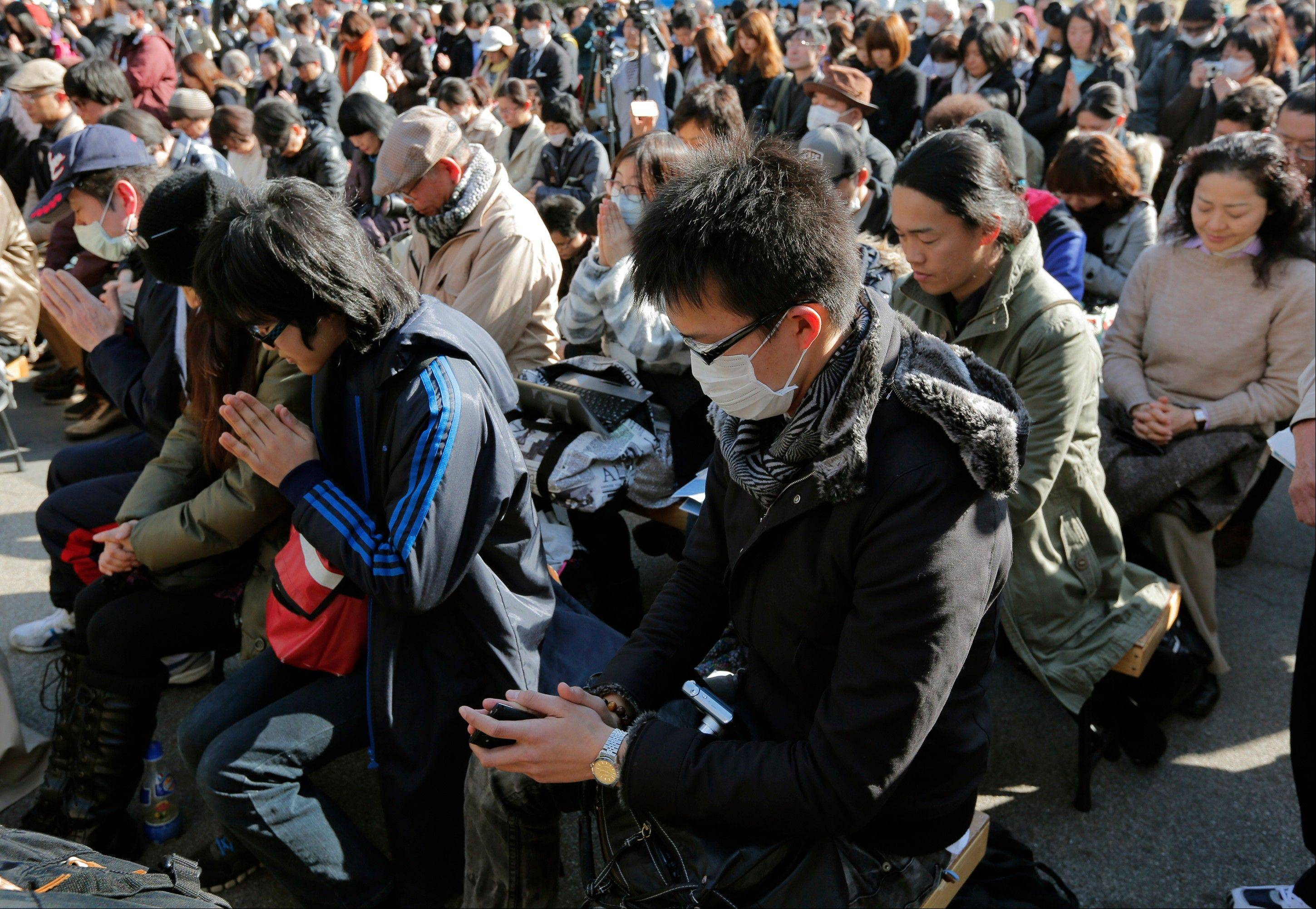People observe a moment of silence for the victims of the March 11, 2011 earthquake and tsunami during an event at a park in Tokyo, Monday, March 11, 2013. Japan marked the second anniversary on Monday of the devastating earthquake and tsunami that left nearly 19,000 people dead or missing.
