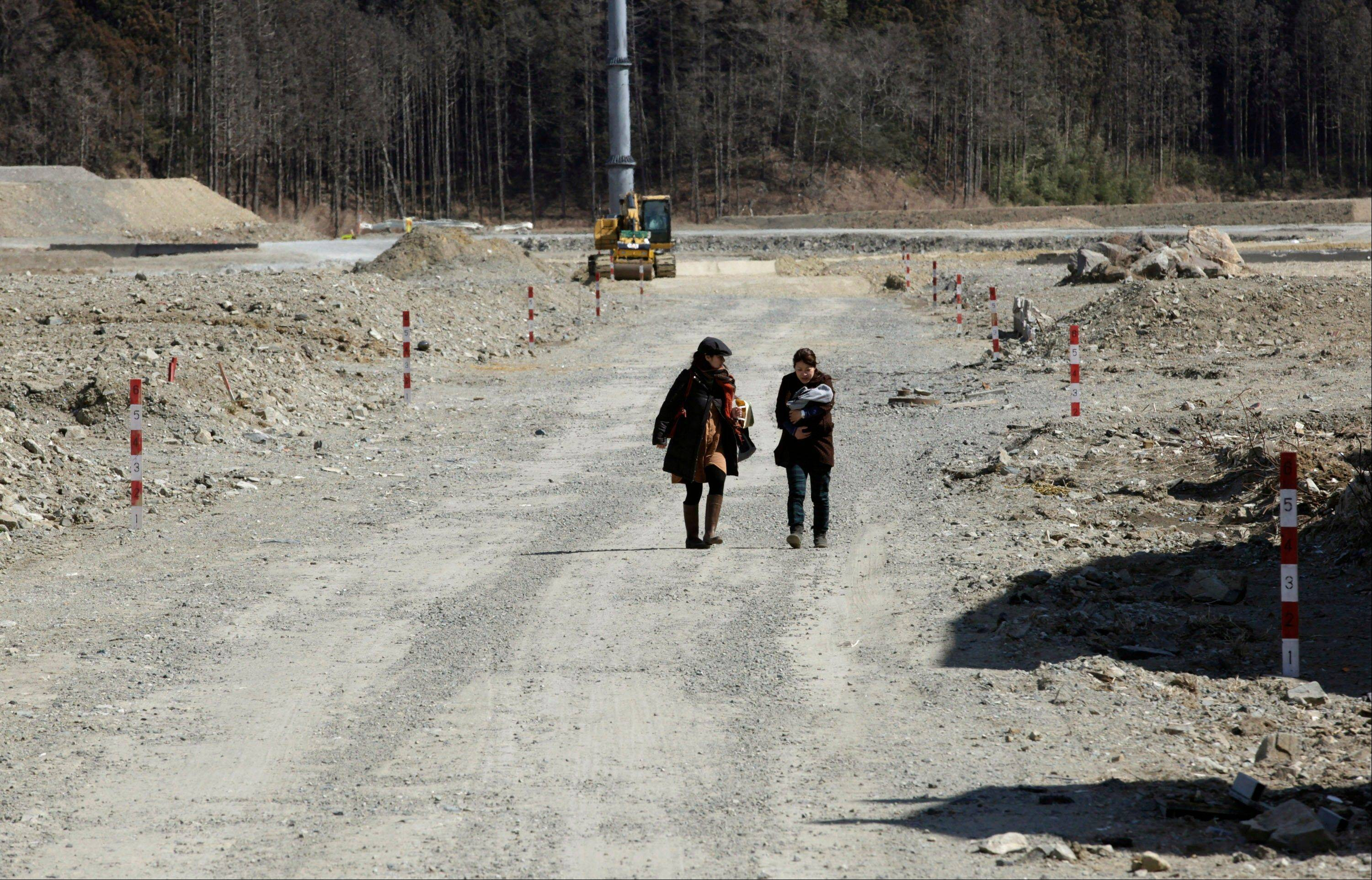 Women approach Okawa Elementary School where 74 of the 108 students went missing after the March 11 tsunami in Ishinomaki, Miyagi prefecture, Japan, Monday, March 11, 2013. The two-year anniversary Monday of Japan's devastating earthquake, tsunami and nuclear catastrophe is serving to spotlight the stakes of the country's struggles to clean up radiation, rebuild lost communities and determine new energy and economic strategies.