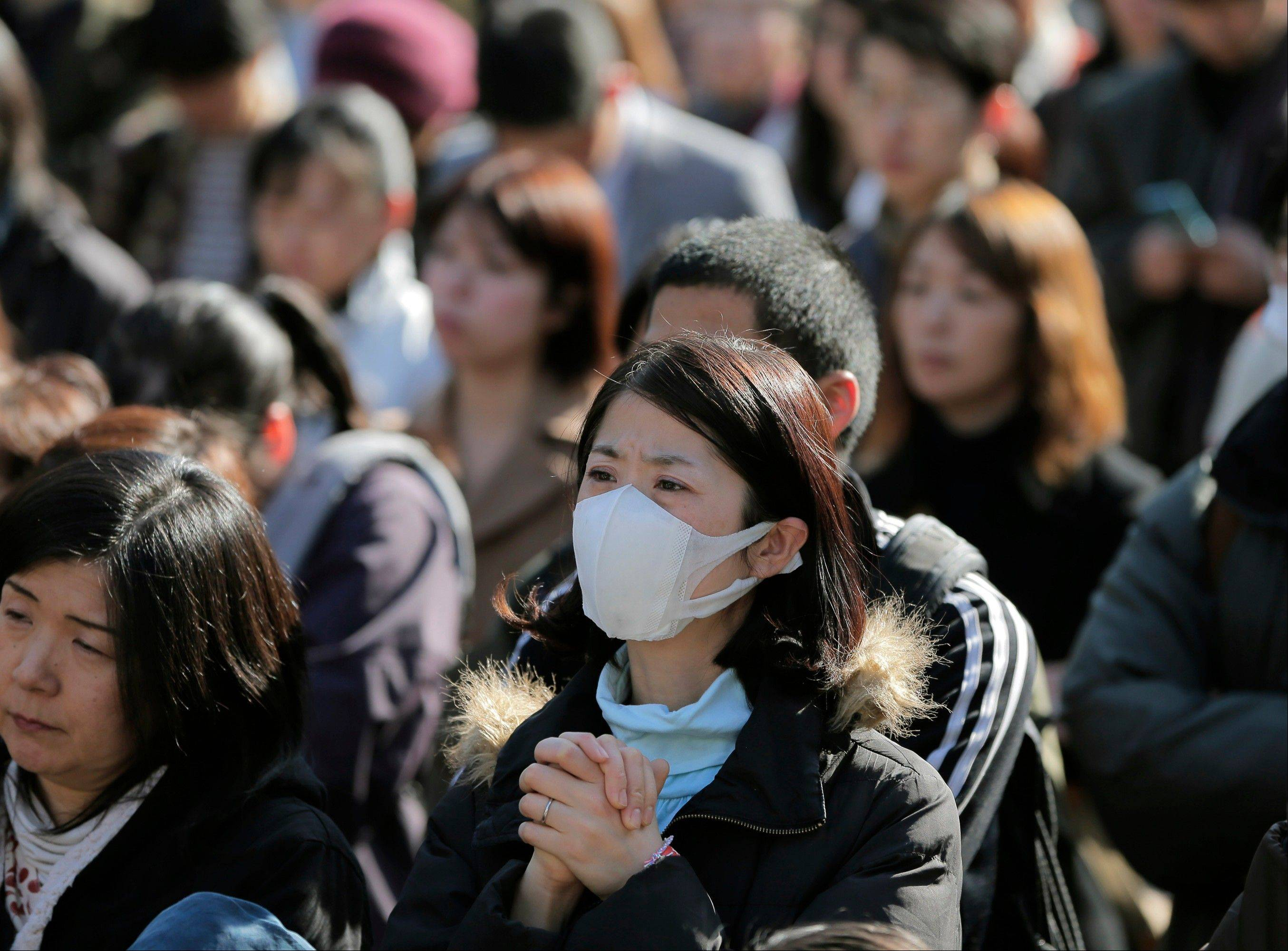 A woman prays during a rally against nuclear power plants as victims of the March 11, 2011 earthquake and tsunami are remembered, at a park in Tokyo, Monday, March 11, 2013. Japan marked the second anniversary on Monday of the devastating earthquake and tsunami that left nearly 19,000 people dead or missing.