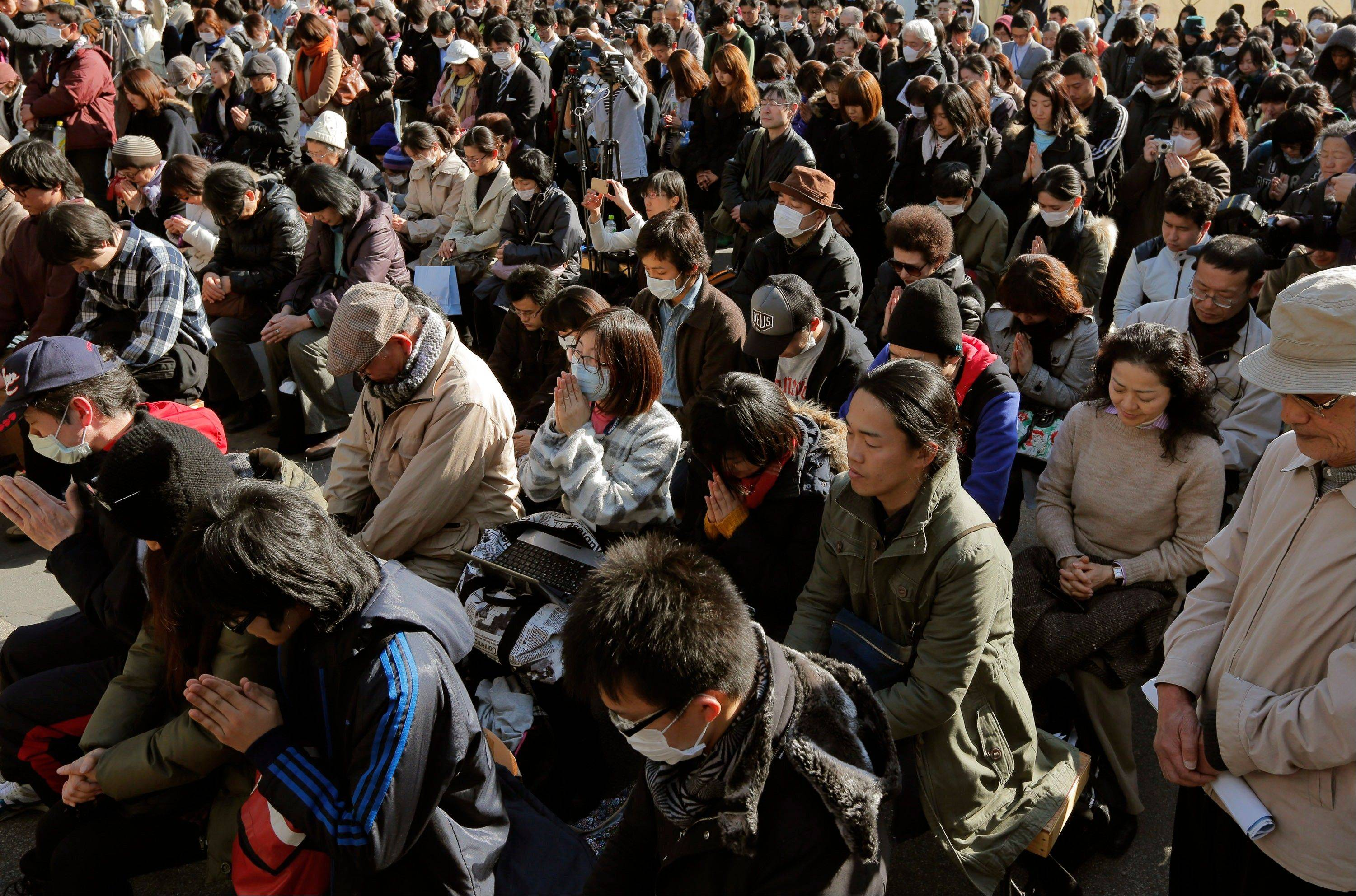 People observe a moment of silence for the victims of the March 11, 2011 earthquake and tsunami during an event at a park in Tokyo, Monday, March 11, 2013.